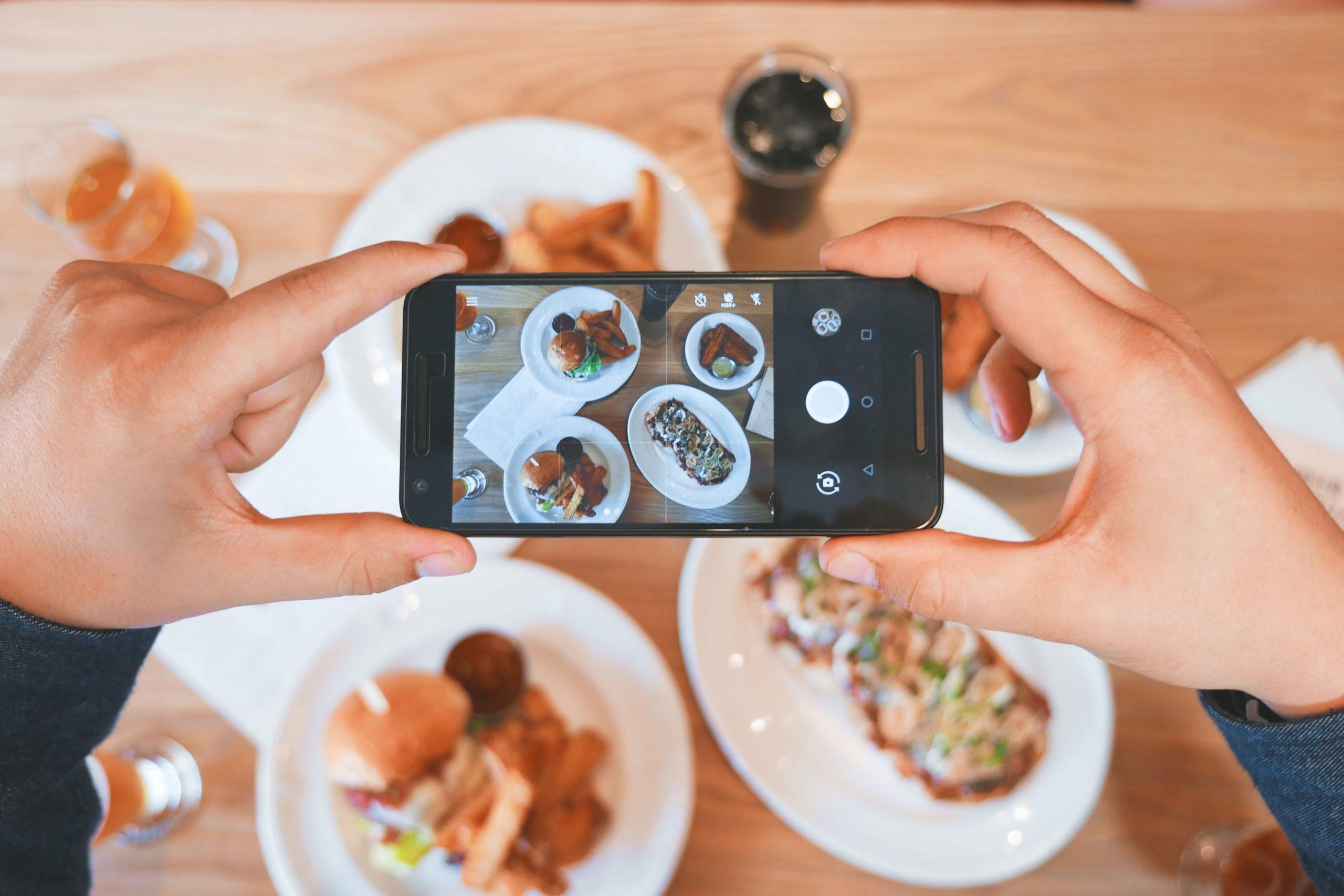 Pessoa fotografando mesa com refeições.
