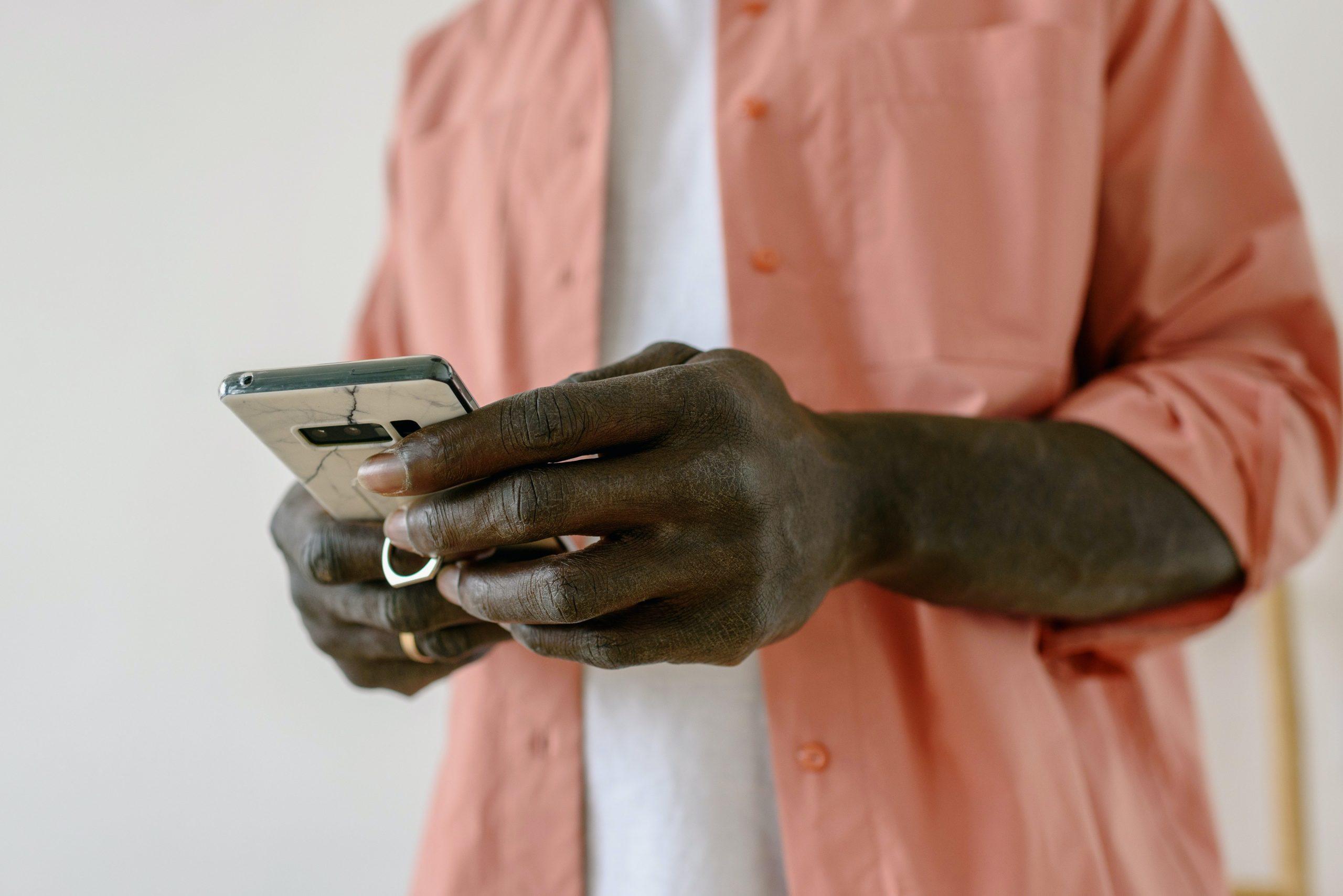Imagem mostra um homem segurando um smartphone.