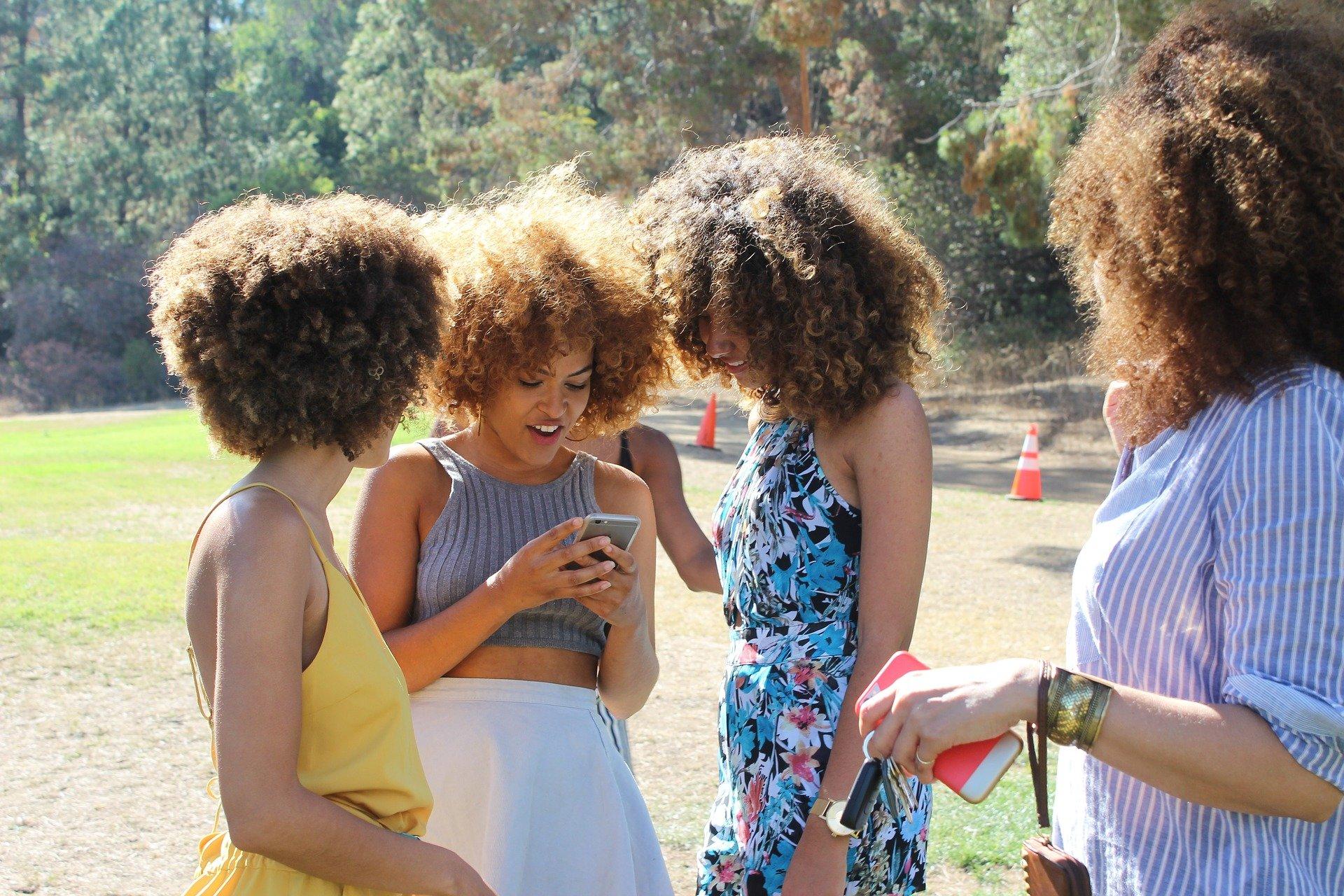 Quatro amigas olhando um Iphone.