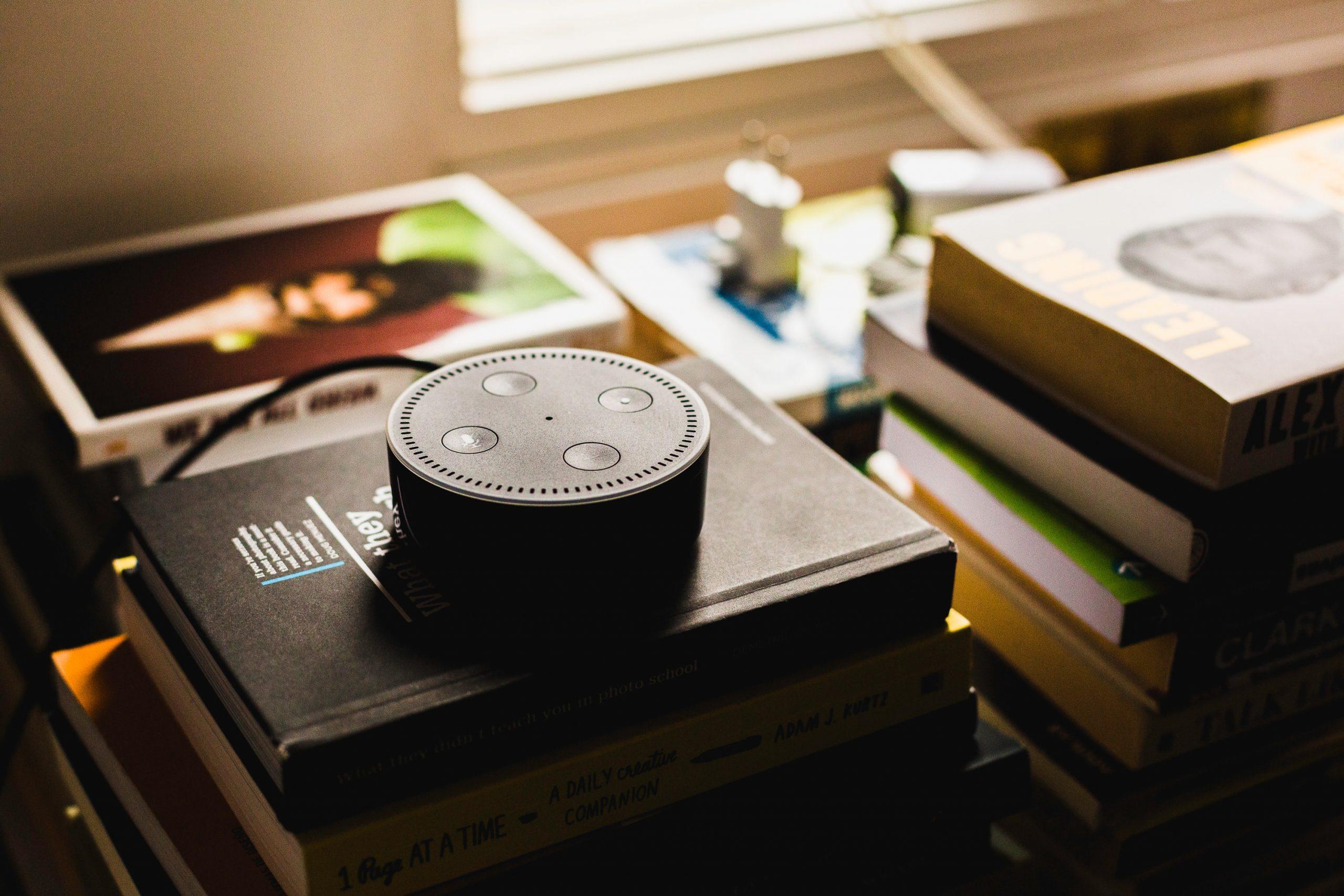 Imagem mostra uma caixa de som de um Amazon Echo sobre uma pilha de livros.