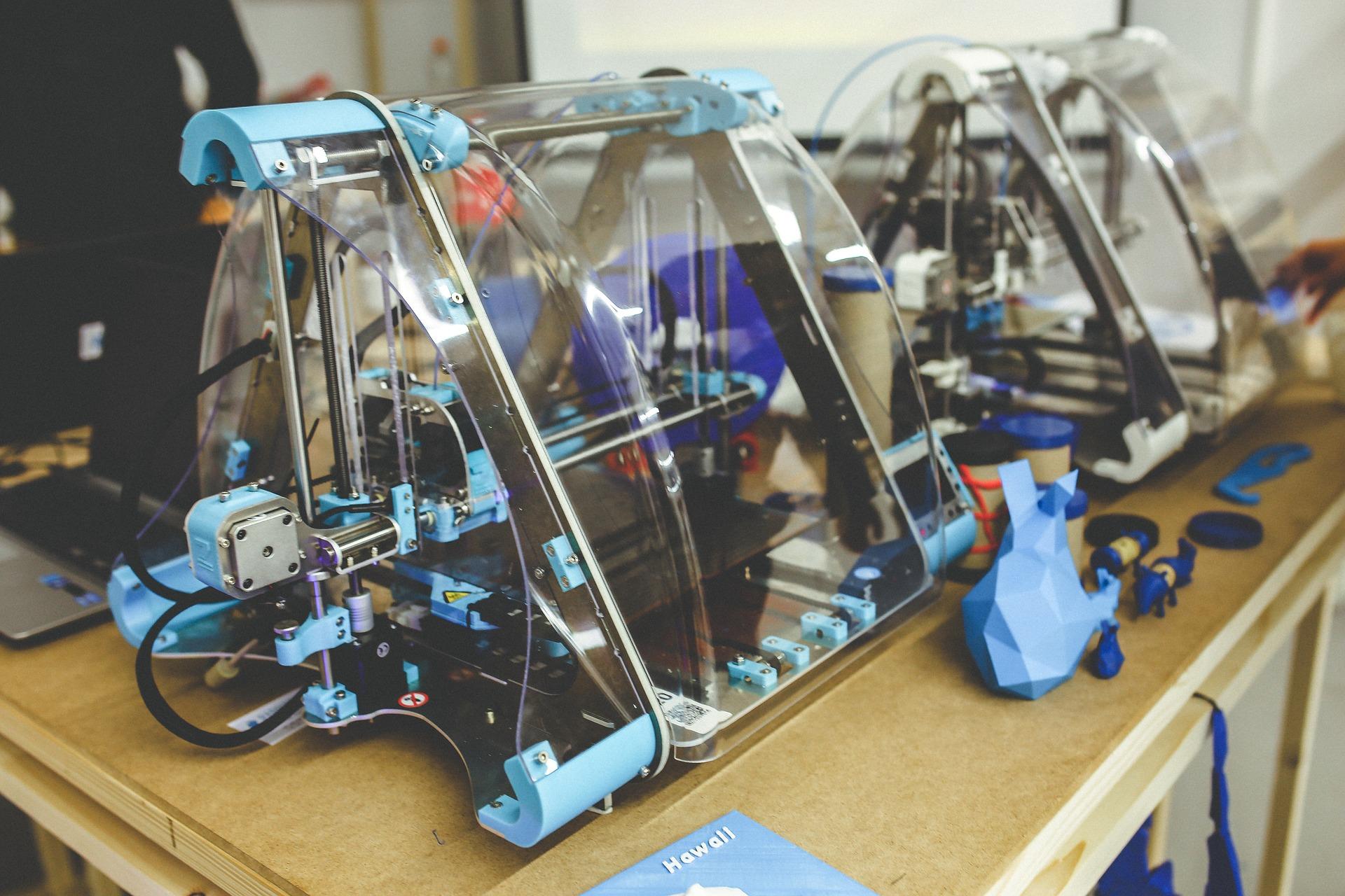 Imagem mostra impressoras 3D lado a lado sobre uma mesa.