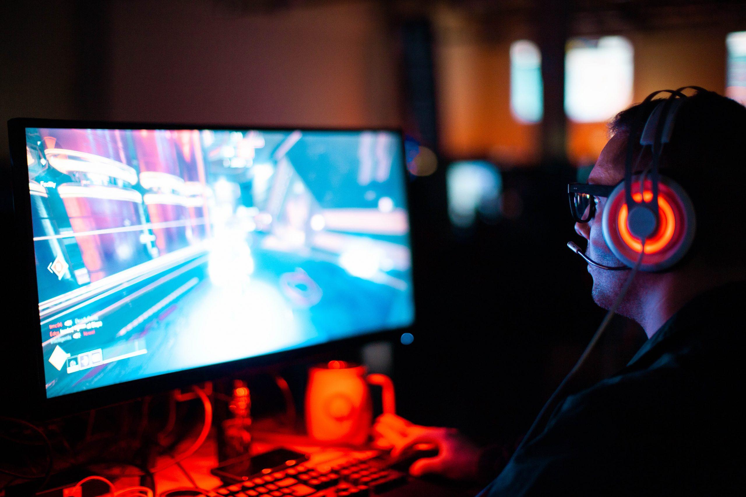 Homem de óculos com utilizando um headset olhando para a tela do computador jogando jogo FPS