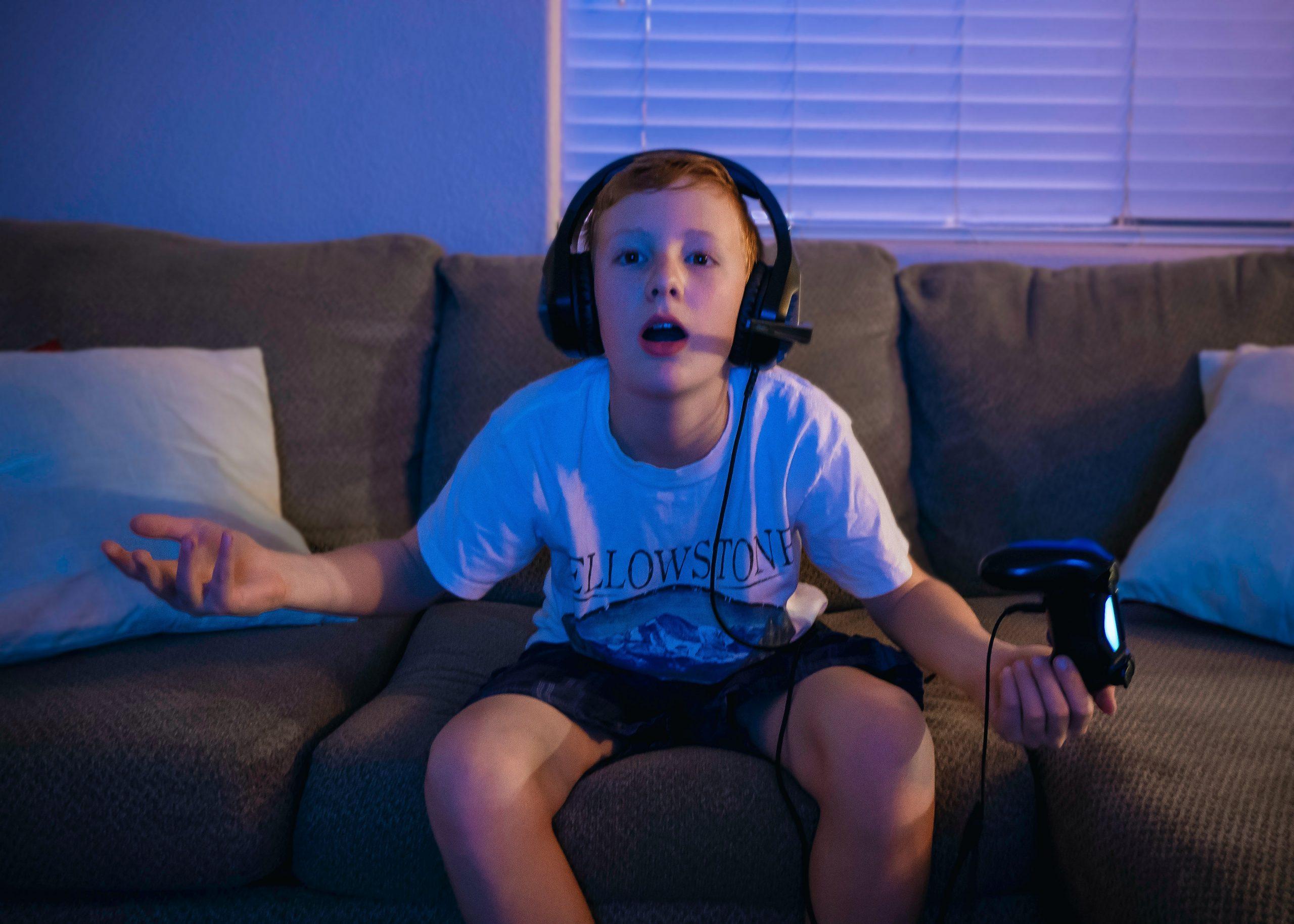 Imagem mostra uma criança sentada no sofá jogando e usando um headset gamer.
