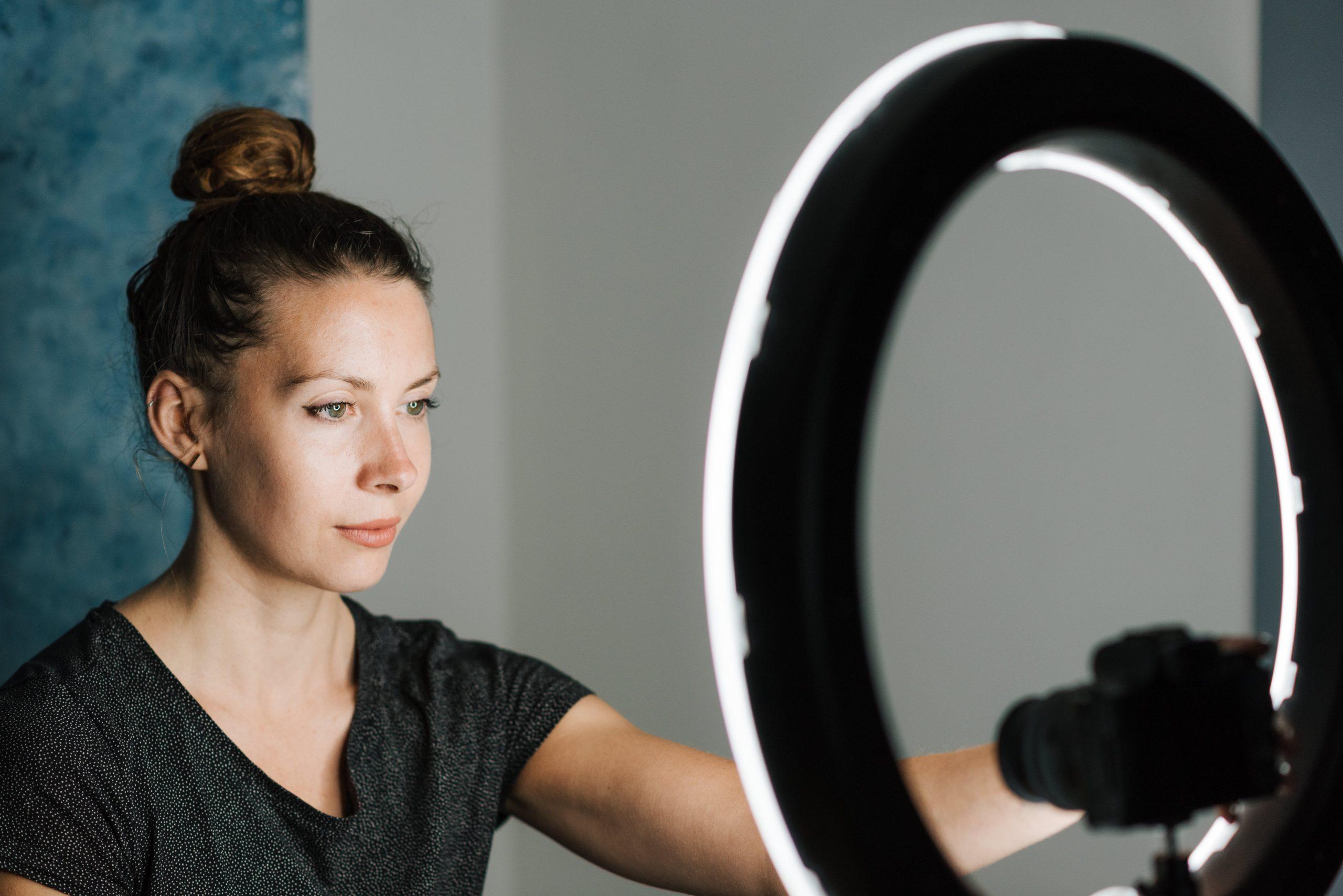Imagem de uma mulher ajustando um ring light.
