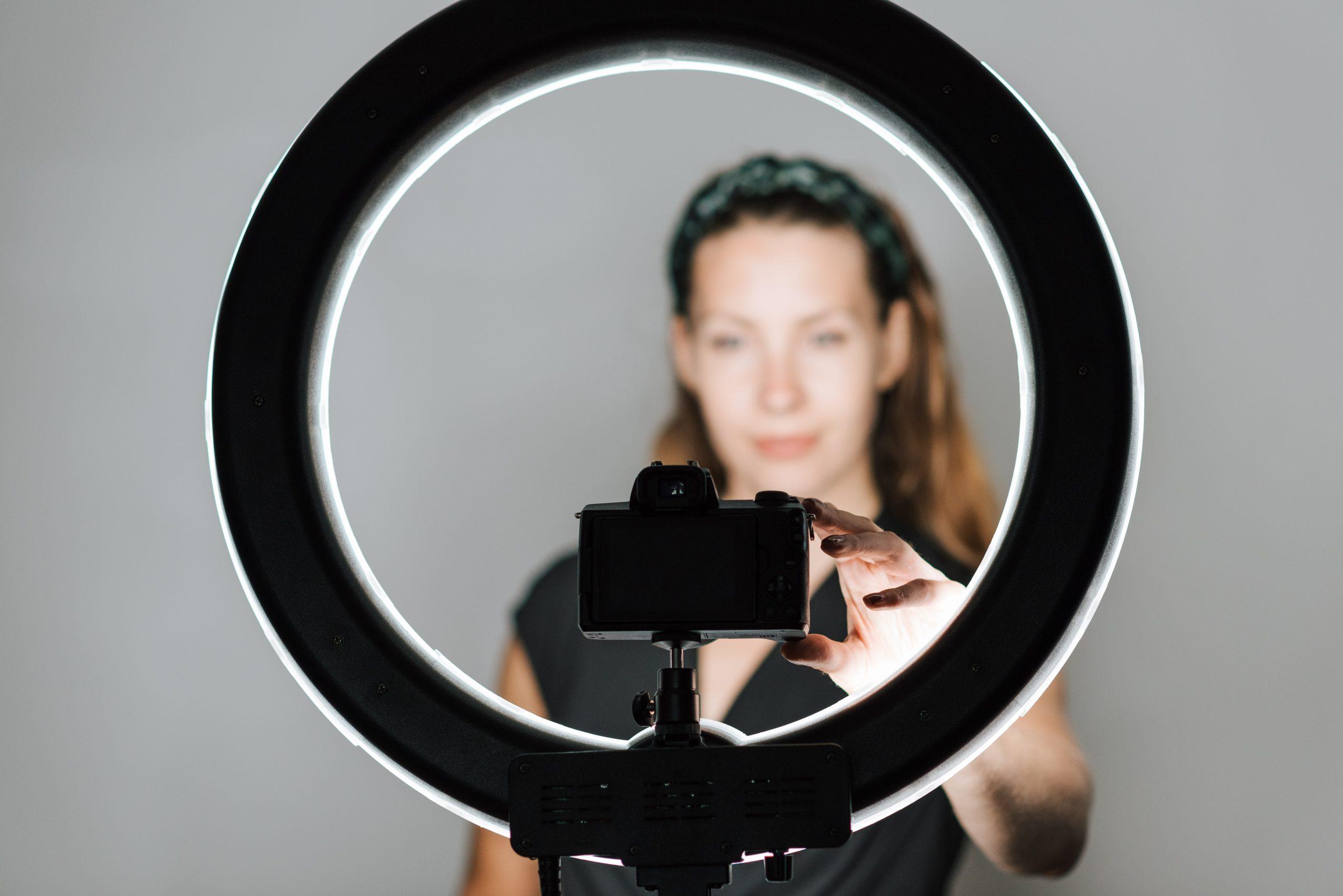 Imagem de uma mulher ajustando a câmera em um tripé com ring light.