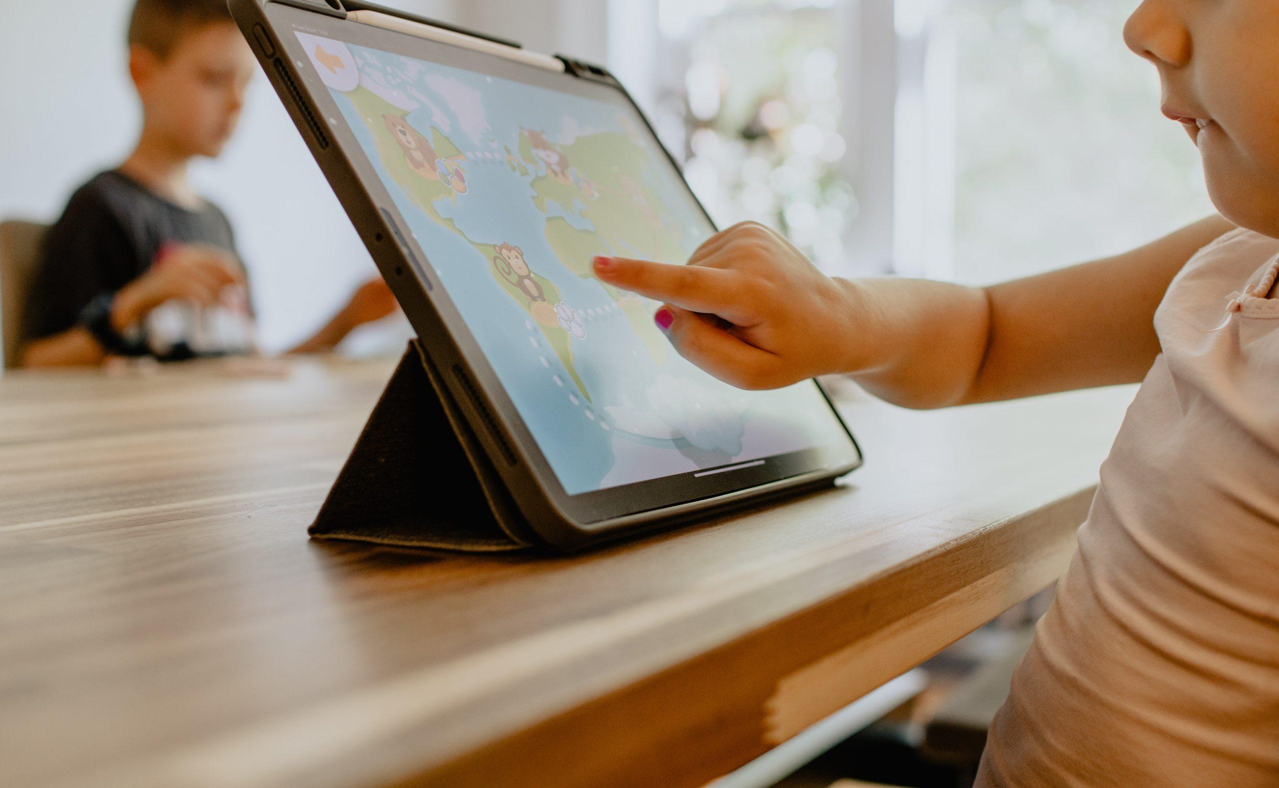 Imagem de uma criança passando o dedo na tela do tablet