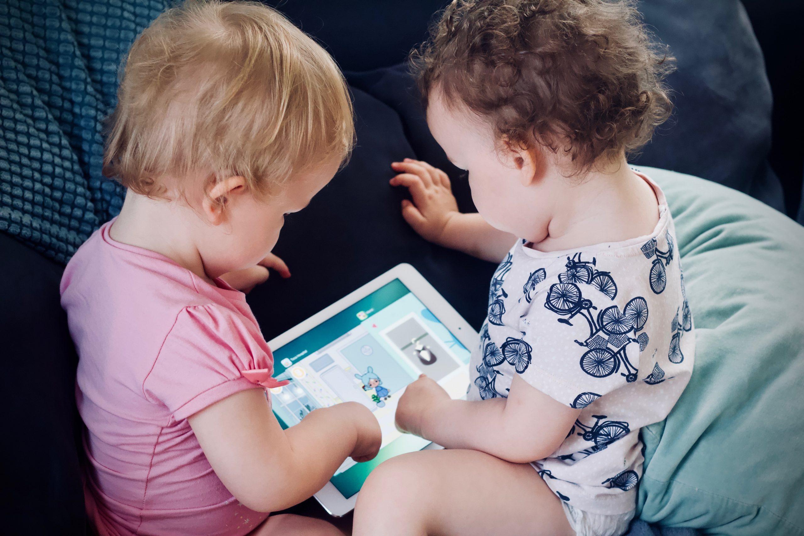 Imagem mostra dois bebês mexendo em um tablet