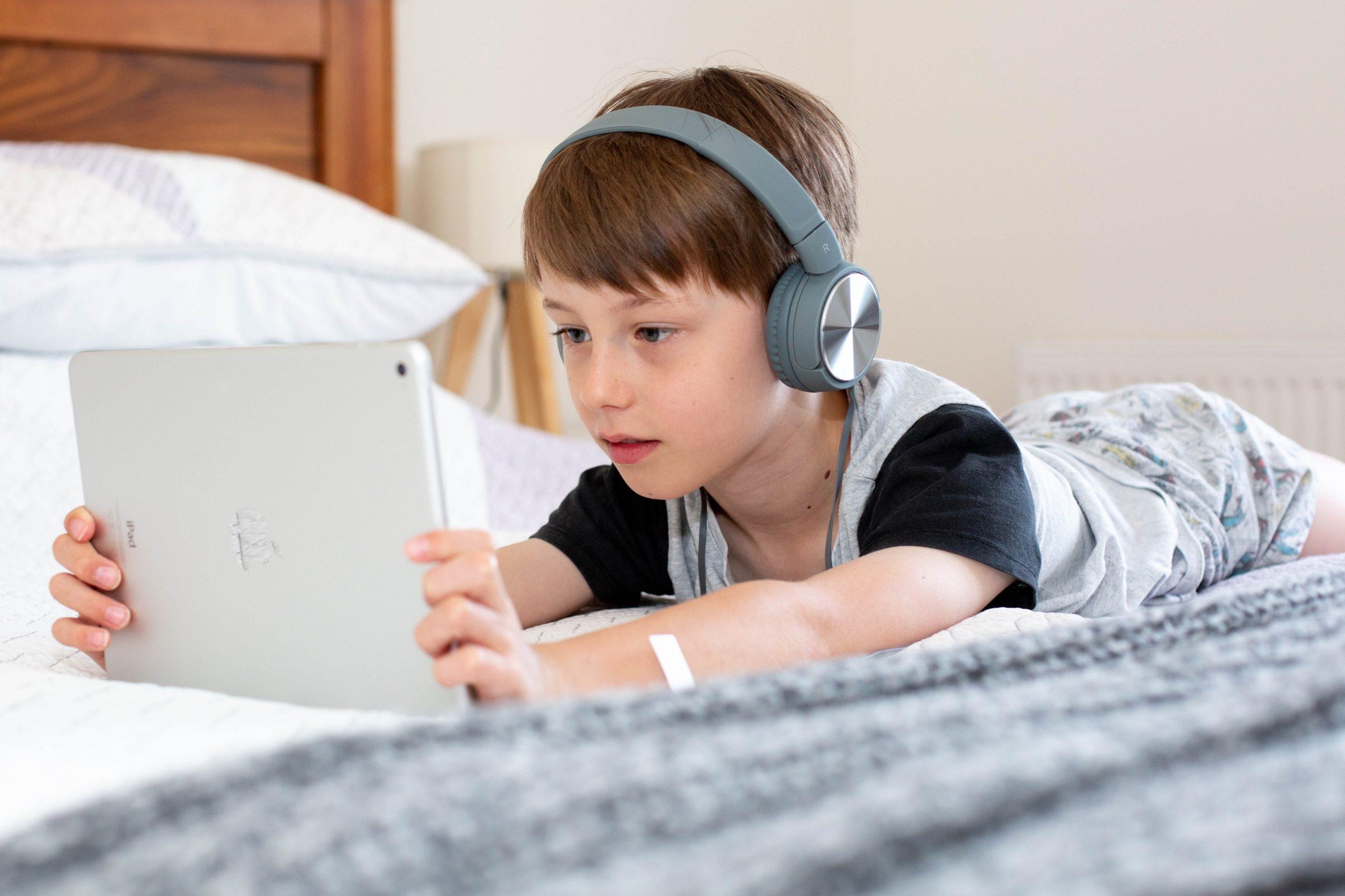 Menino deitado de barriga para baixo na cama segurando tablet e usando fone de ouvido