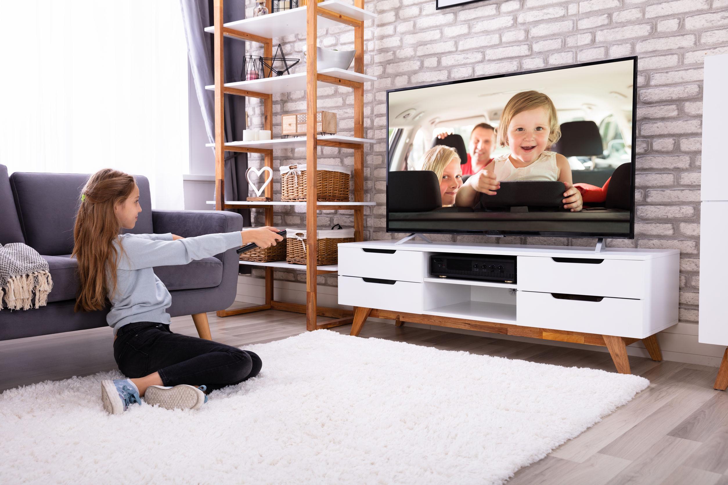 garota na sala assistindo a TV 4k
