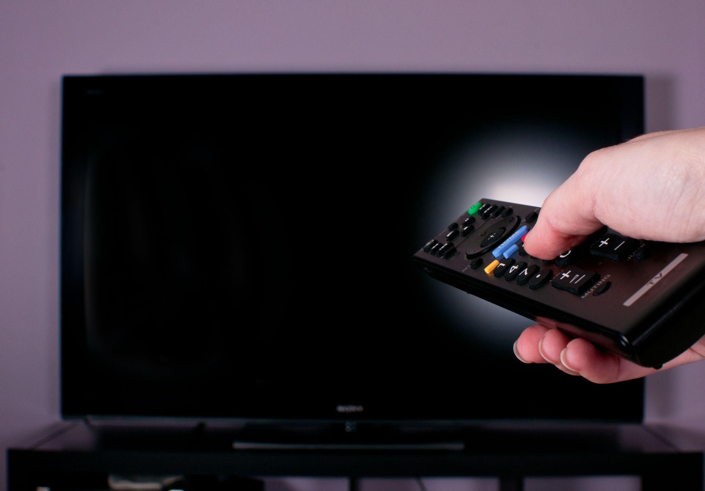 Controle remoto com uma TV 4k ao fundo
