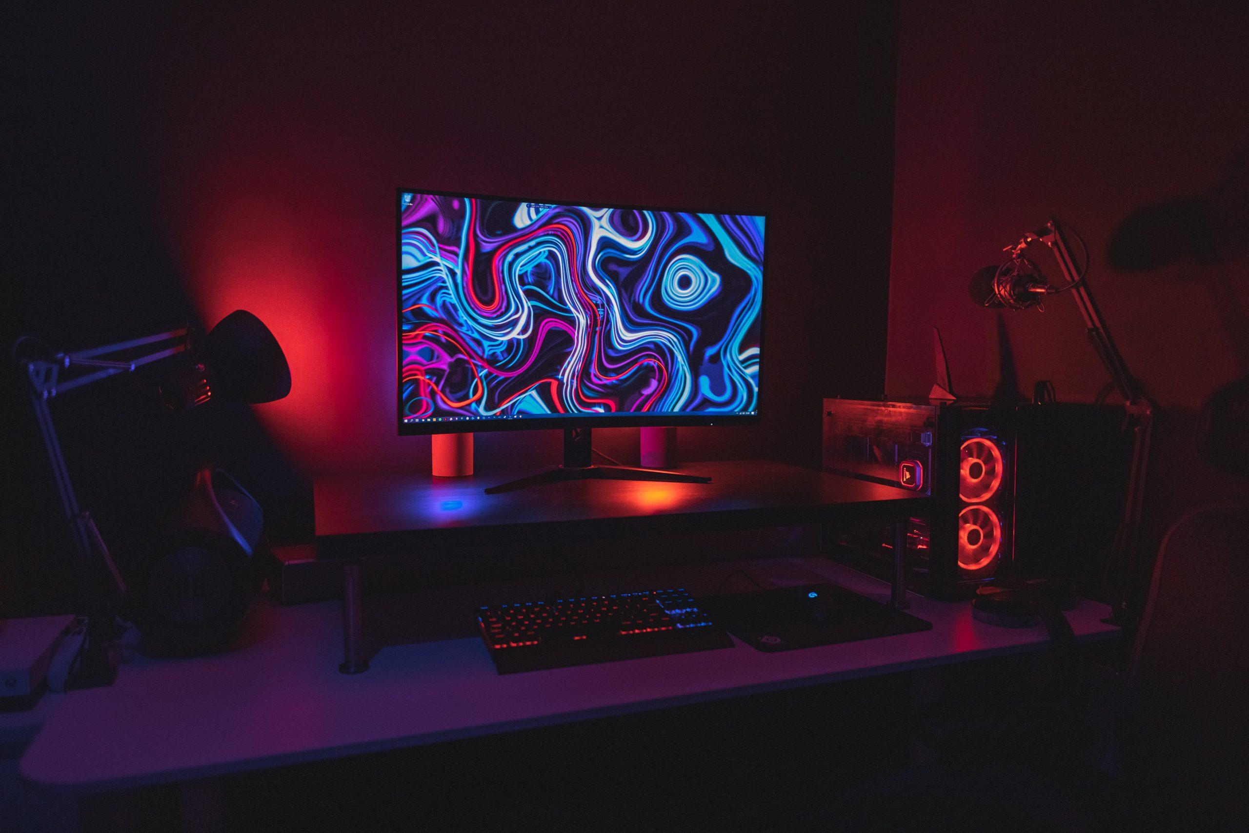 Computador gamer em cima de uma mesa gamer, em uma sala escura com luzes RGB em destaque