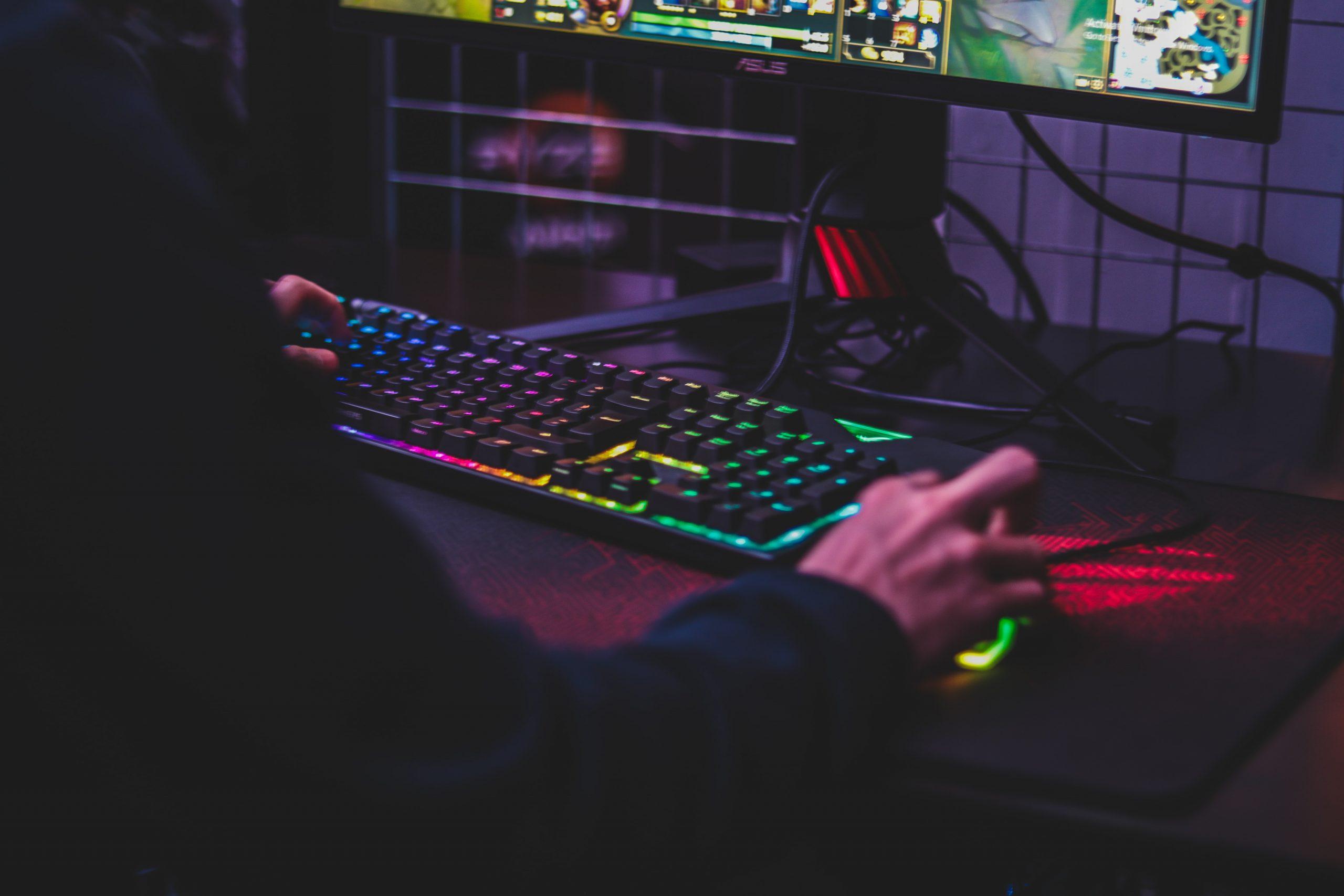 Gamer utilizando o computador, com uma mão no teclado e a outra no mouse.