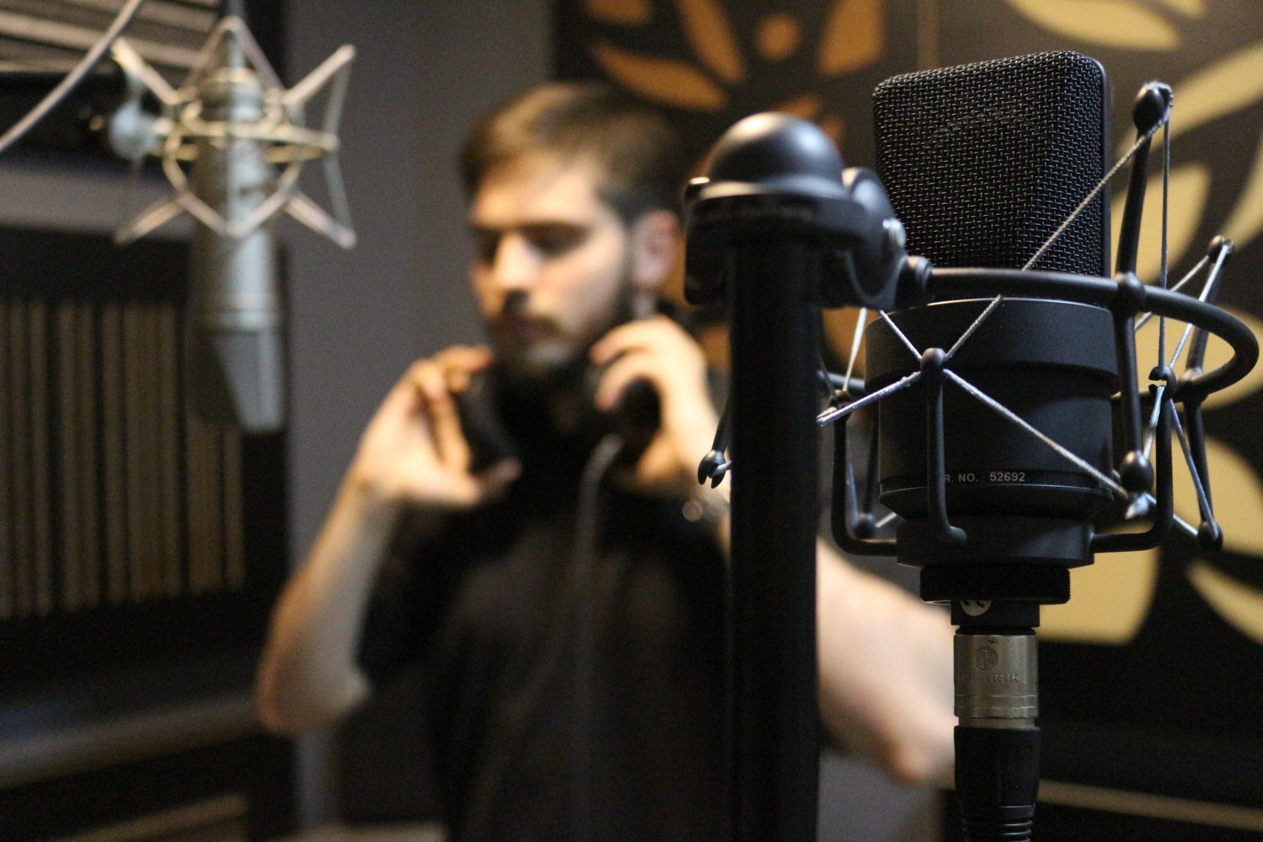 microfone condensador preto em um primeiro plano, com homem ao fundo em pé com as mãos segurando o fone de ouvido