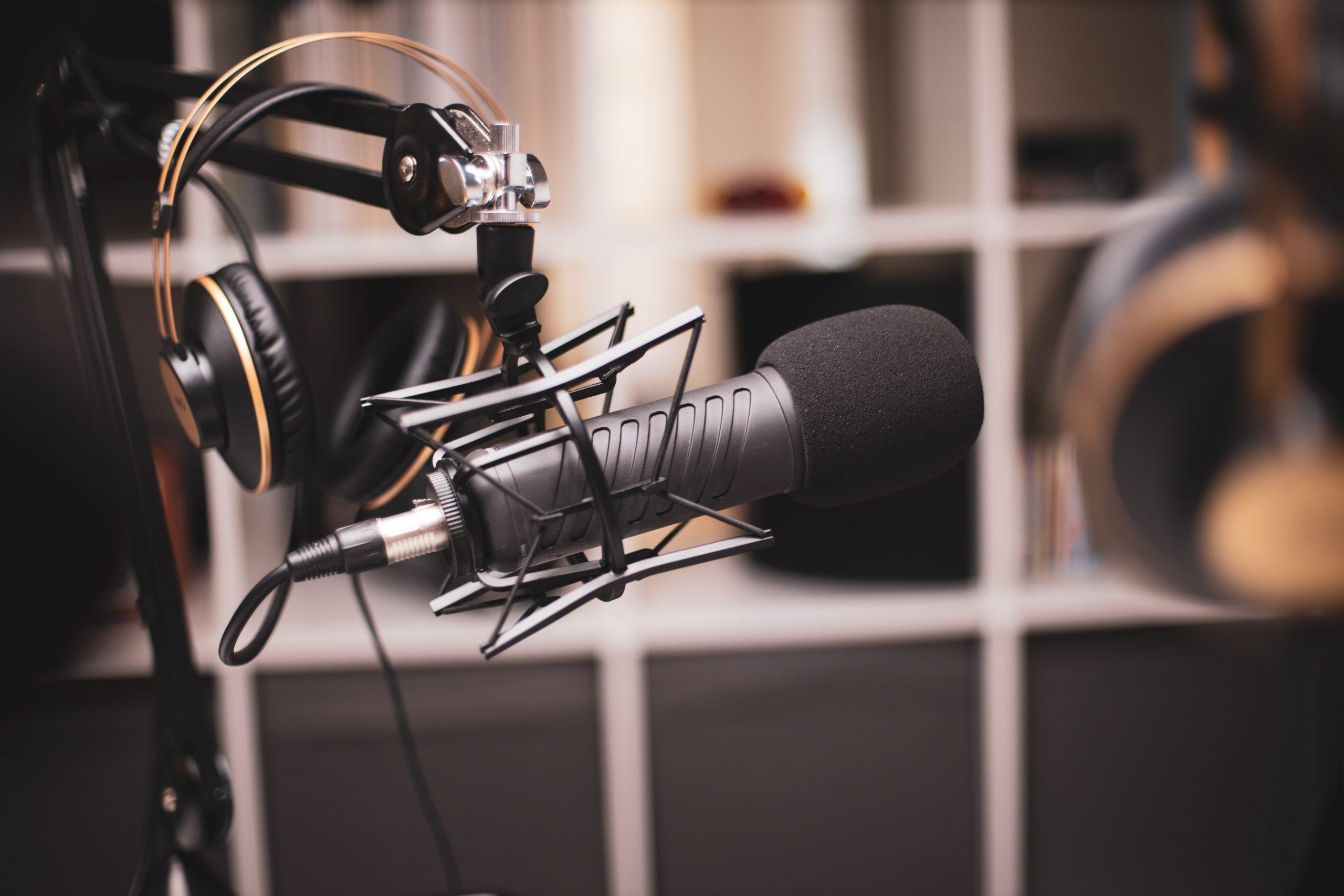 Microfone condensador cinza em um estúdio de gravação com headset ao fundo