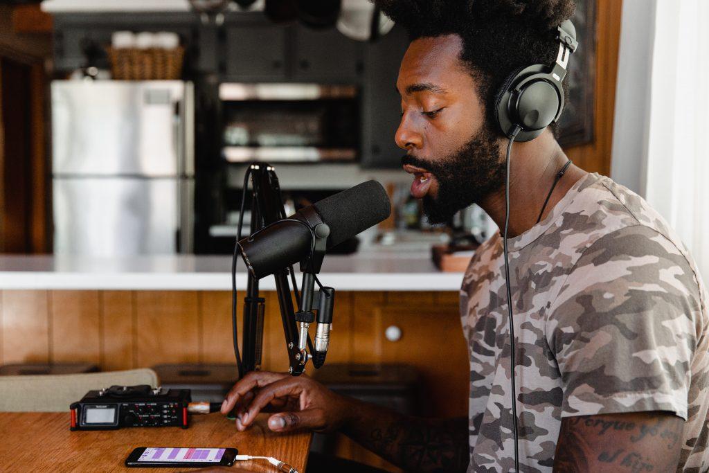 Homem falando em um microfone condensador com headsets na cabeça
