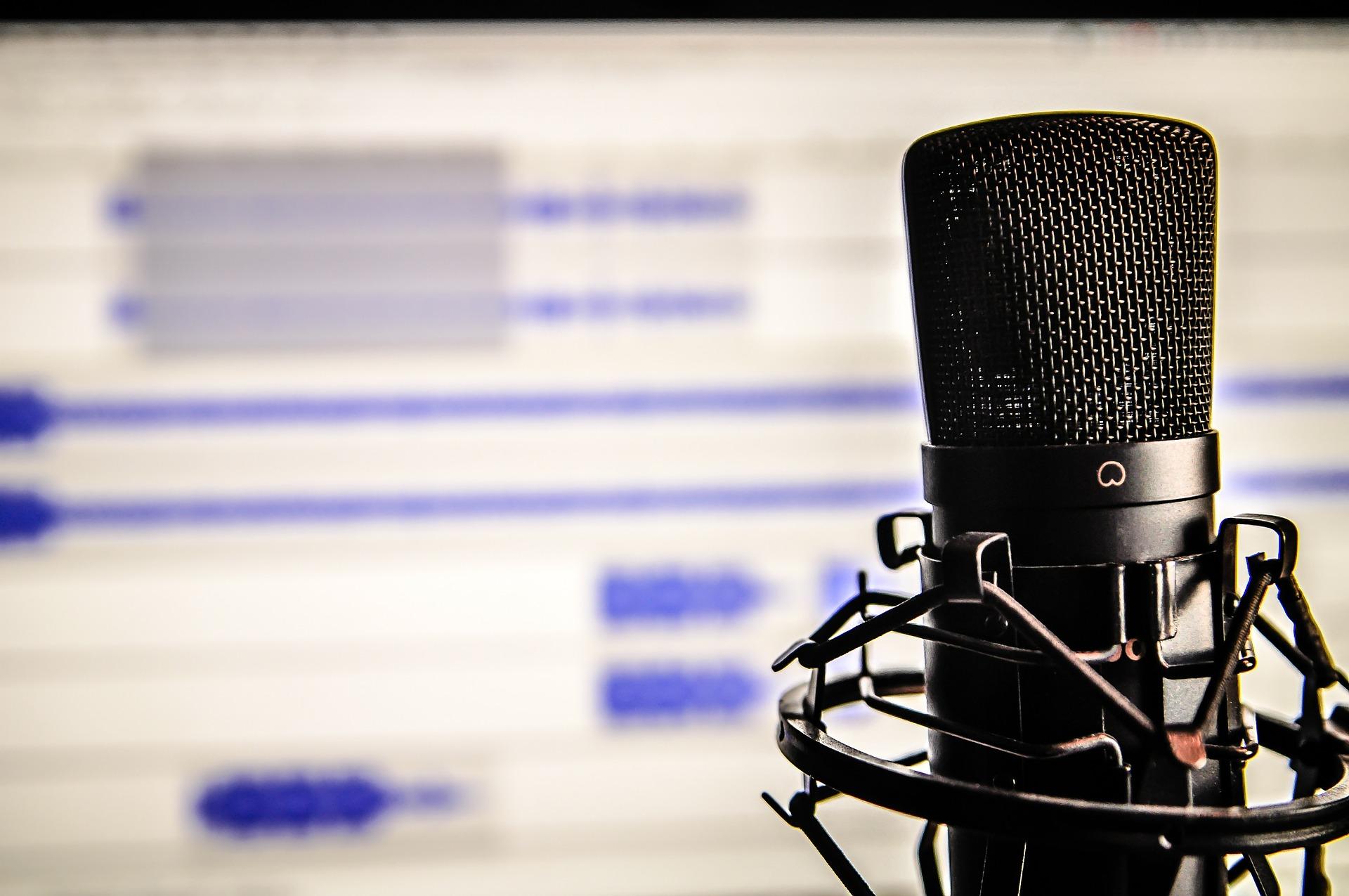 Imagem mostra um microfone em frente a um computador com software de edição aberto.