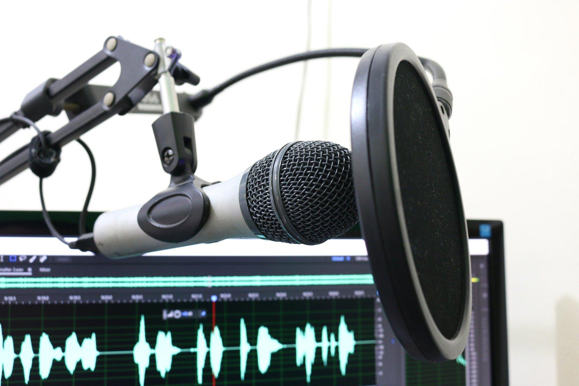 Imagem mostra um microfone com um filtro de ruído em frente a um computador.