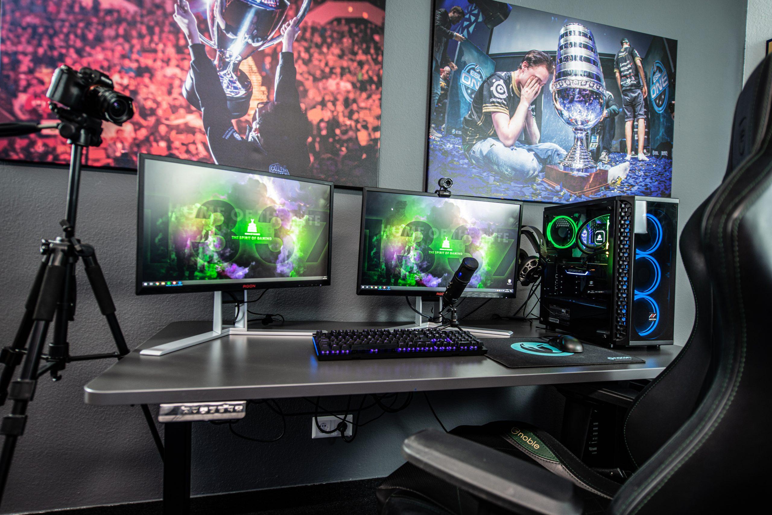 Espaço gamer profissional equipado com mesa gamer na cor cinza e computador gamer e demais periféricos na cor preta