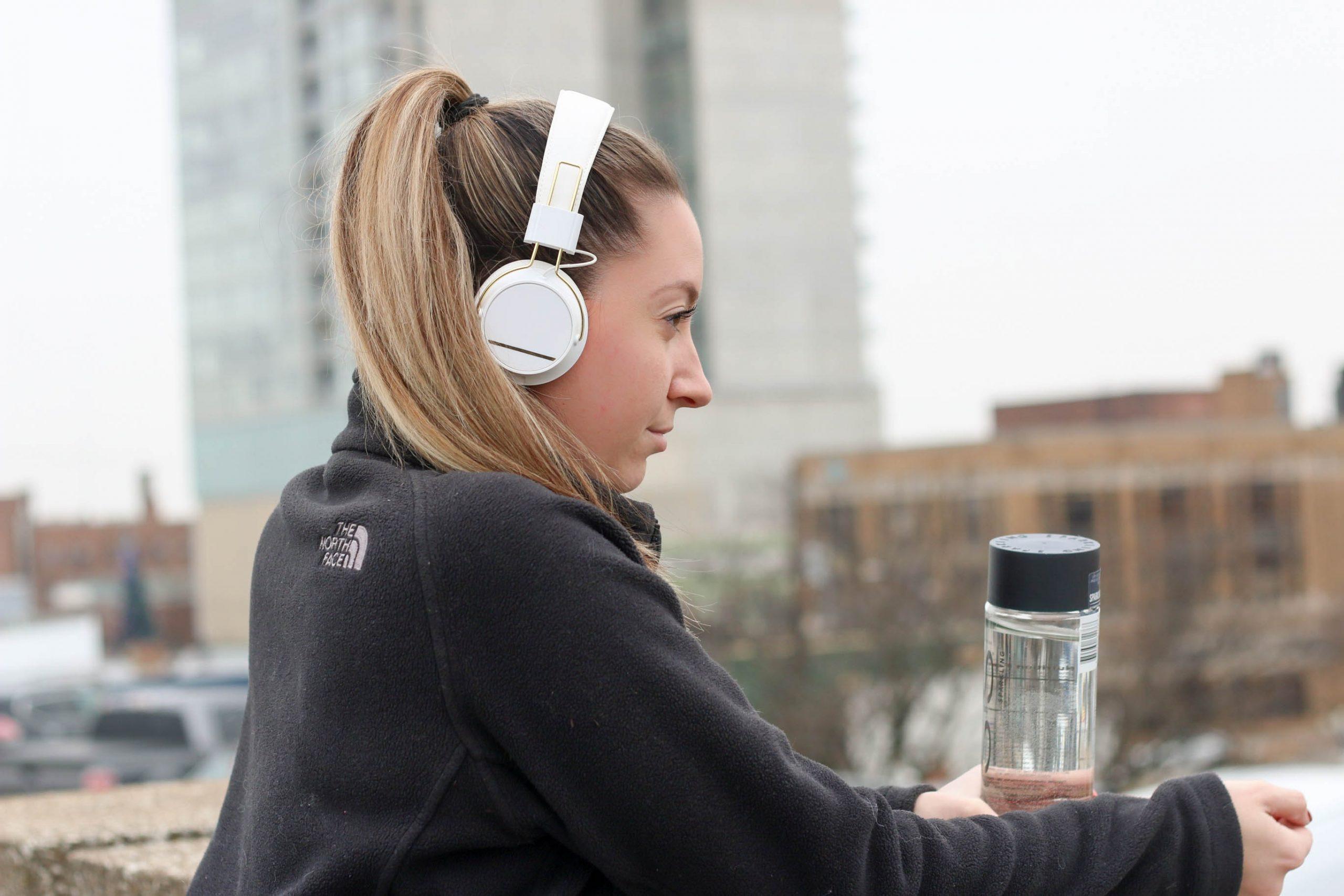 Mulher com roupa de atividade física, fone de ouvido e garrafa d'água de perfil