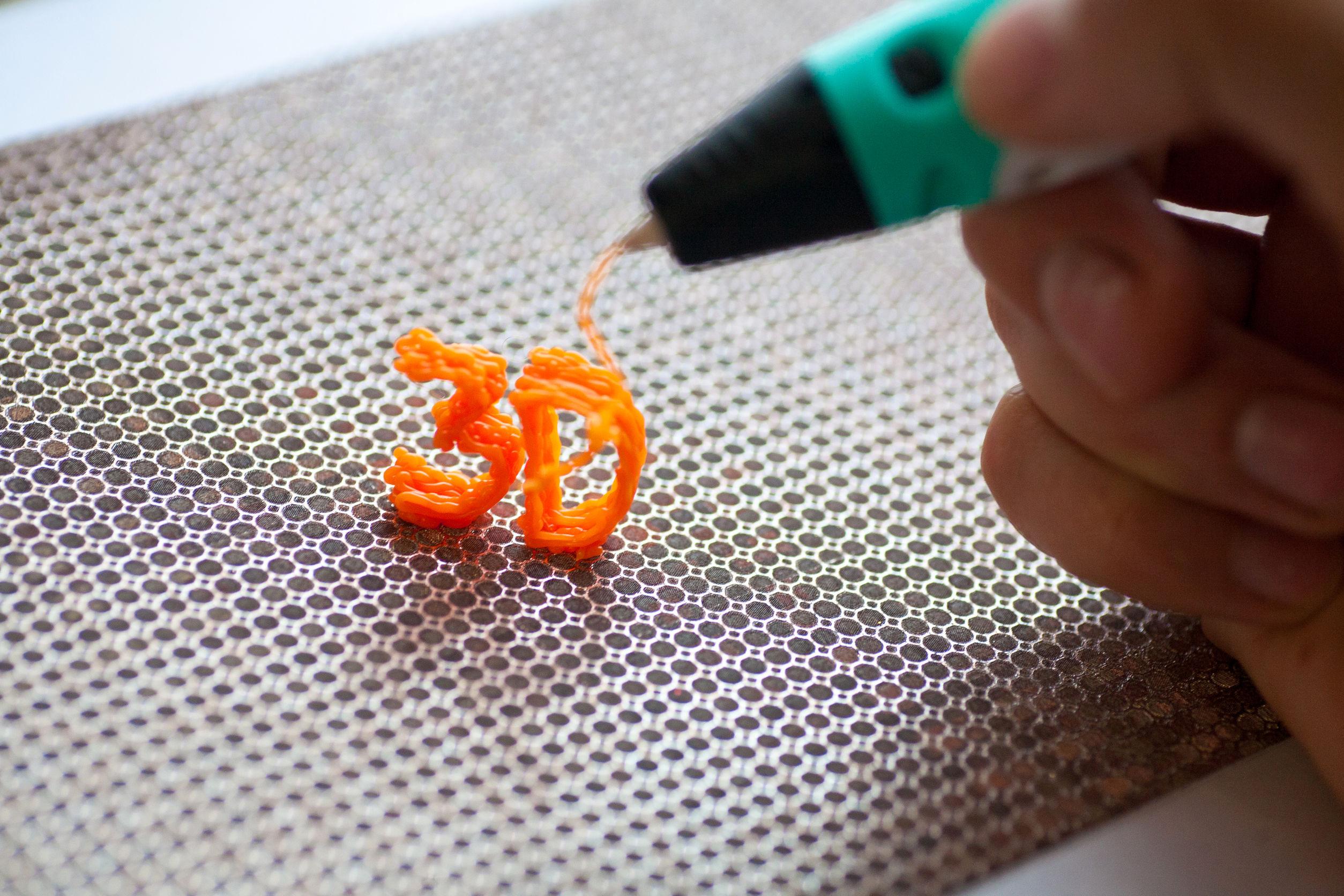 Imagem mostra uma pessoa usando uma caneta 3D para um trabalho artesanal.