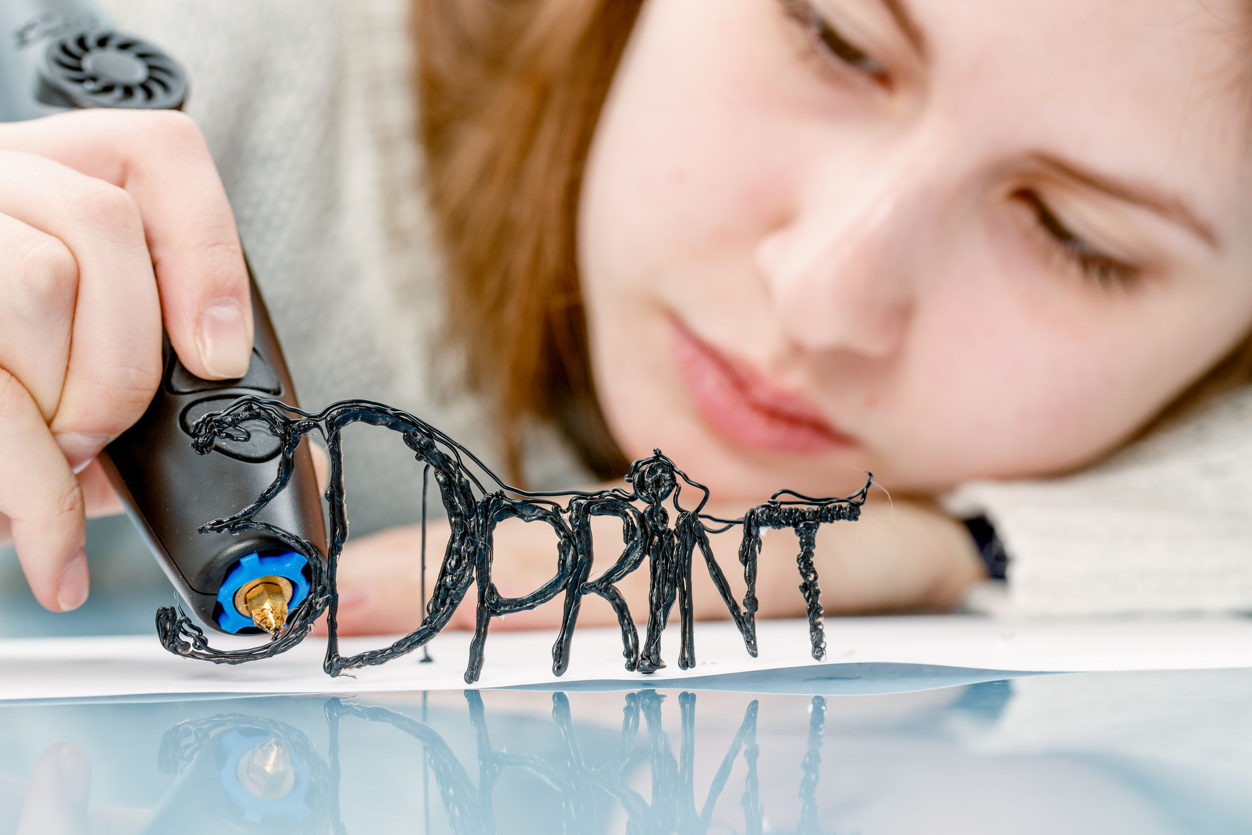 Imagem mostra uma mulher fazendo um trabalho artesanal com uma caneta 3D.
