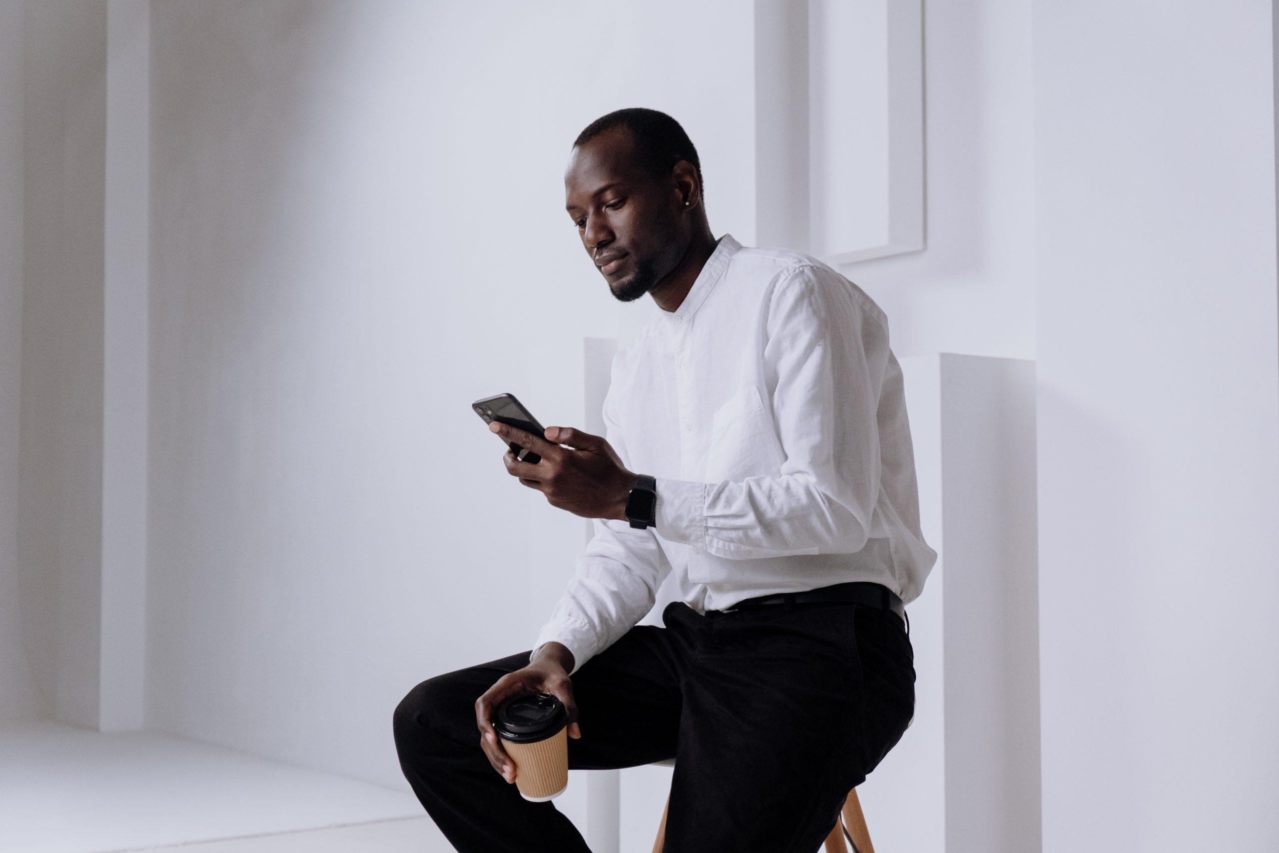 Imagem de um homem navegando em seu smartphone.