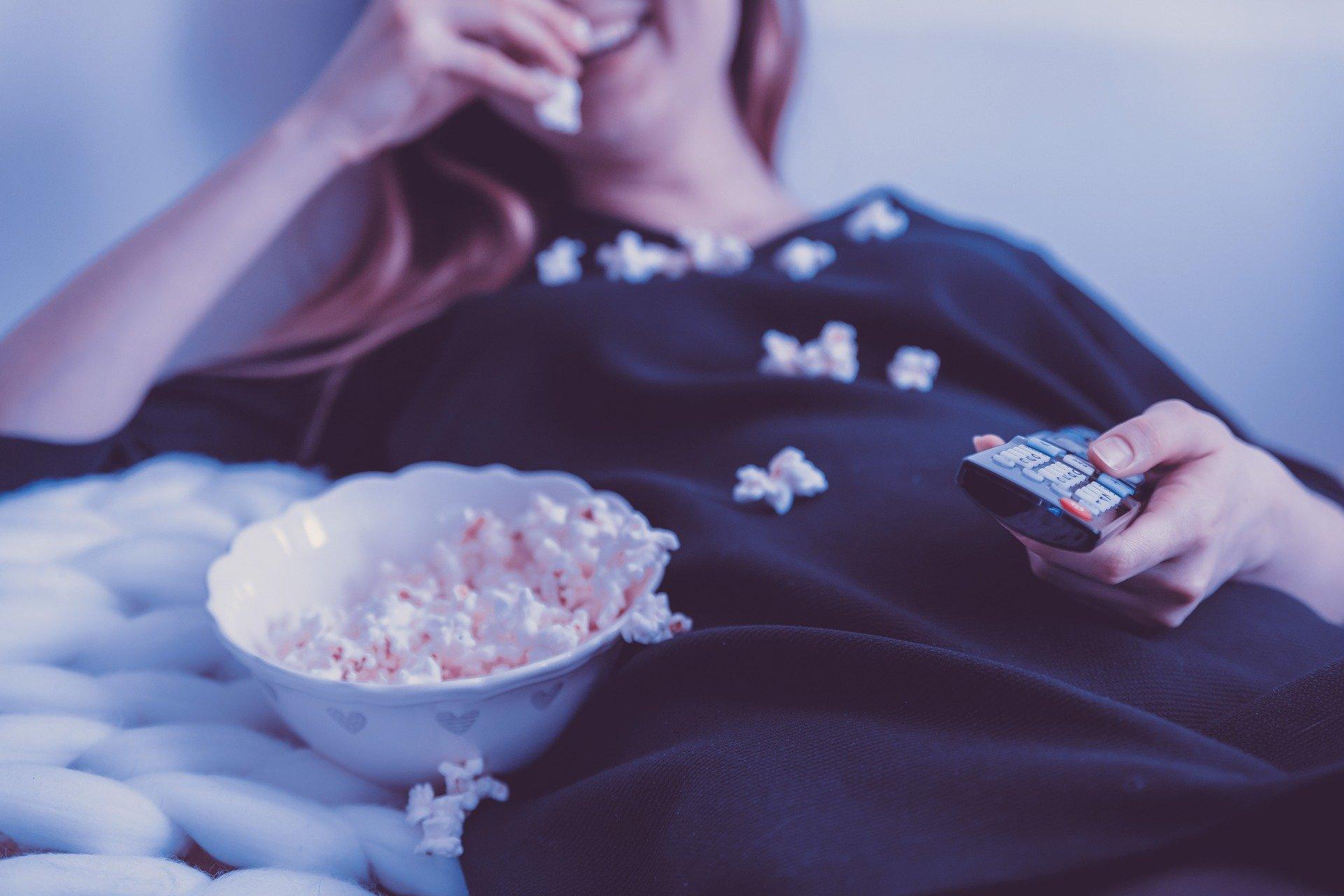 Mulher comendo pipoca e segurando o controle remoto.