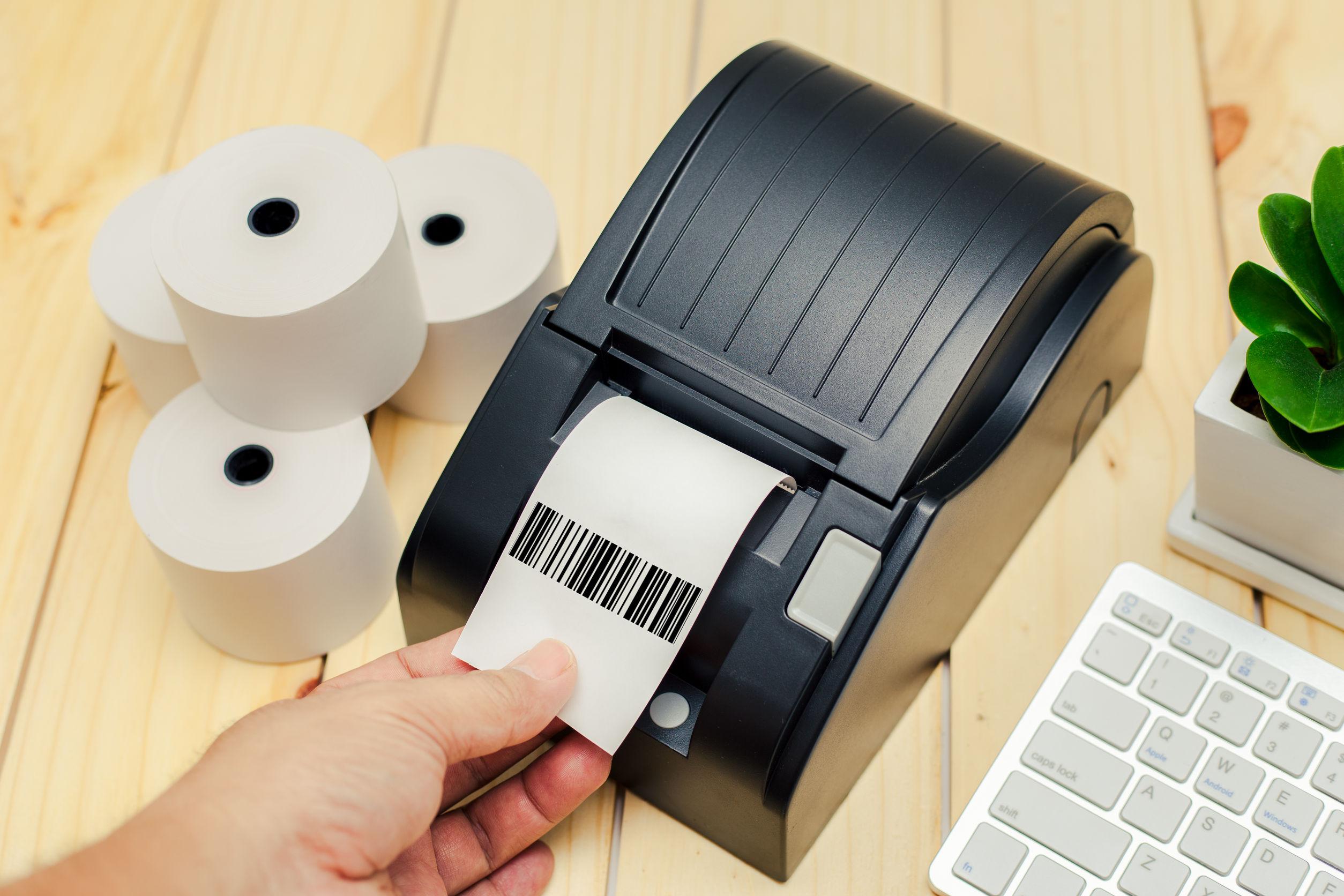Imagem mostra uma pessoa apertando um botão de uma impressora térmica.