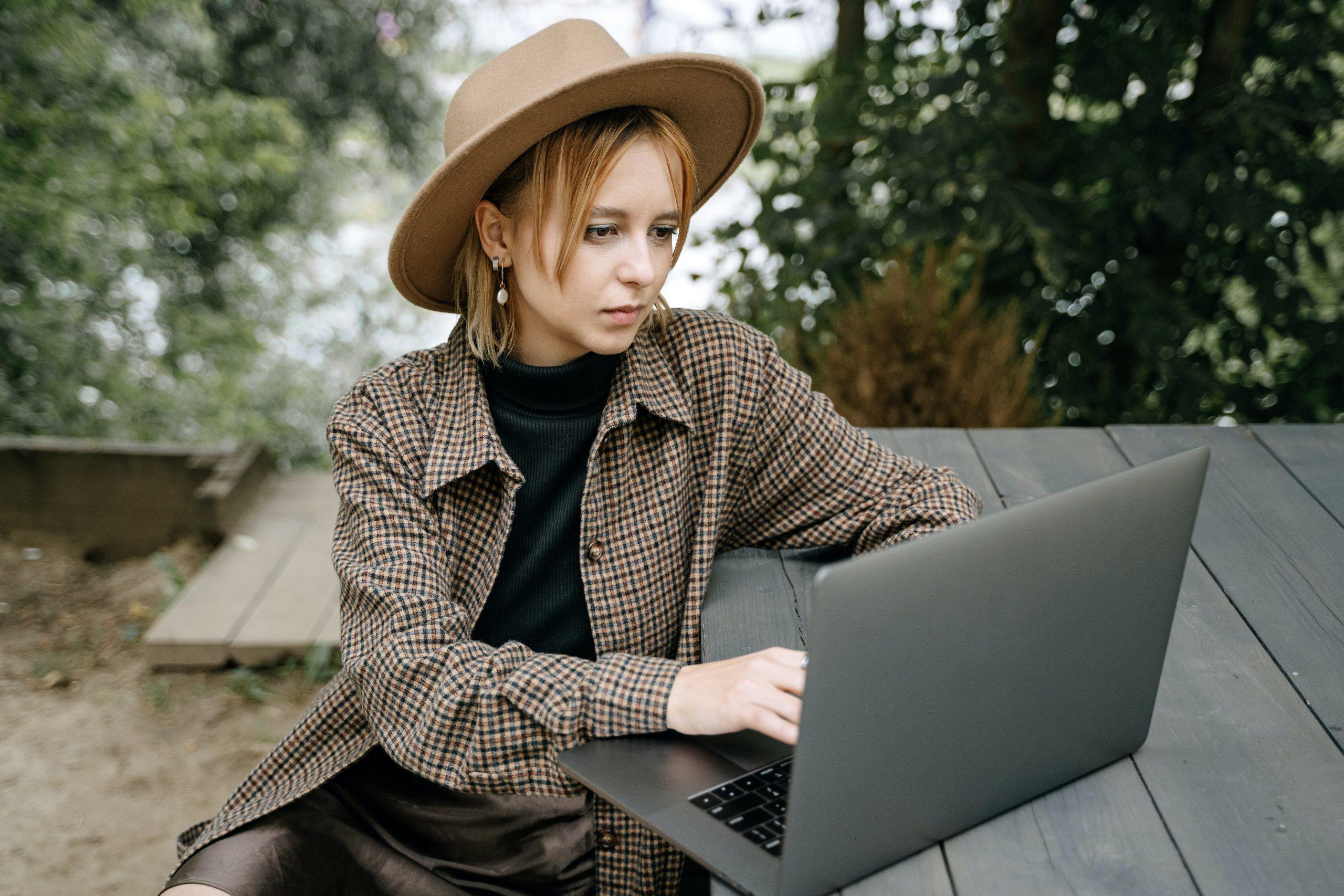 Imagem mostra uma mulher usando um notebook em uma área externa.