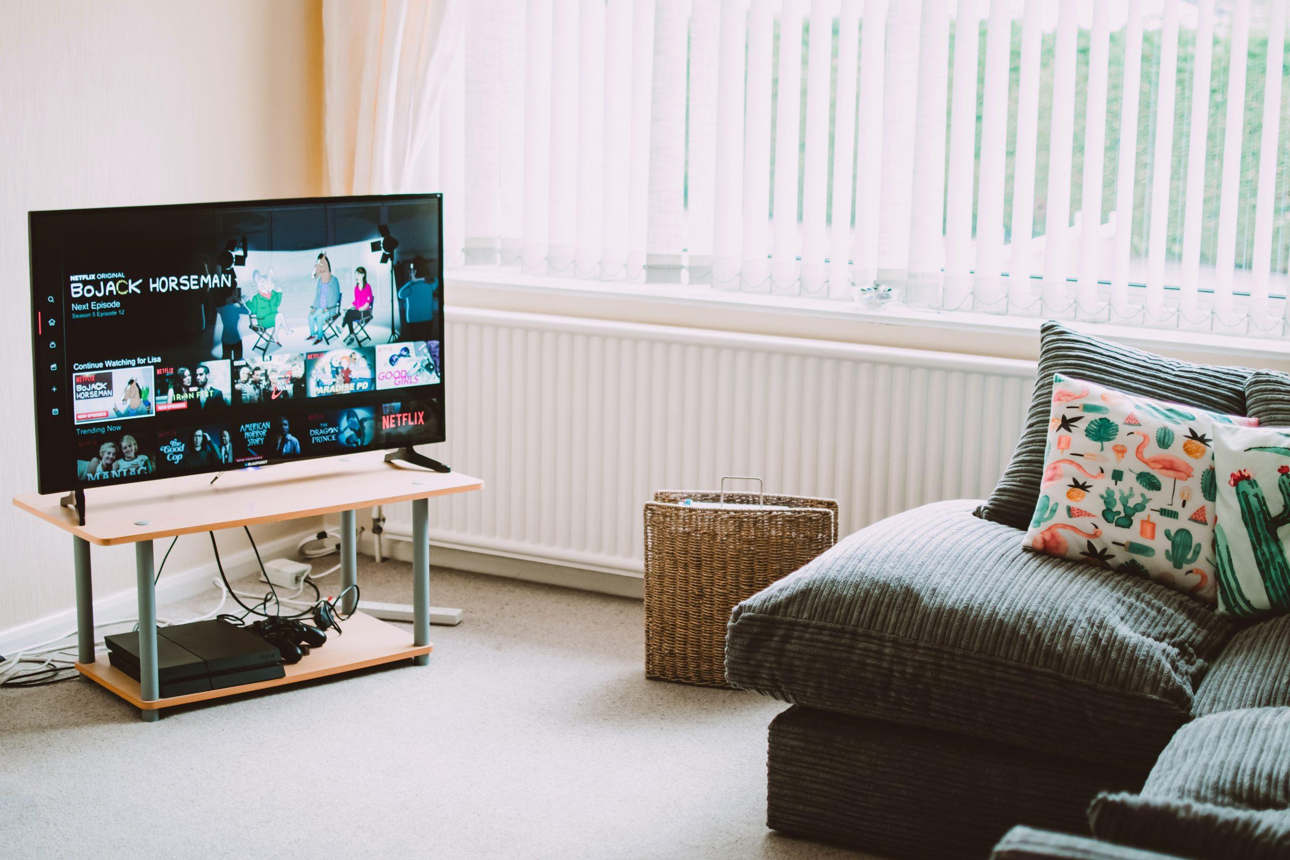Imagem mostra uma TV ligada em uma sala de estar.