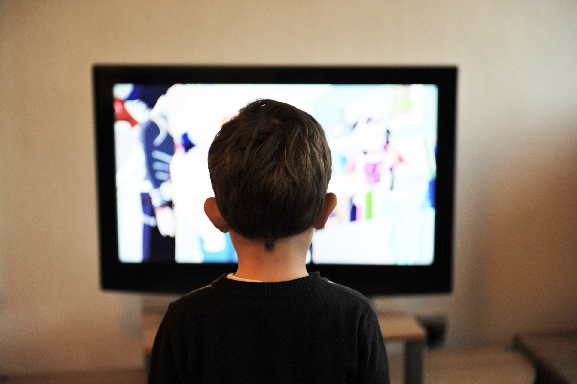 Imagem mostra uma criança assistindo a uma televisão.