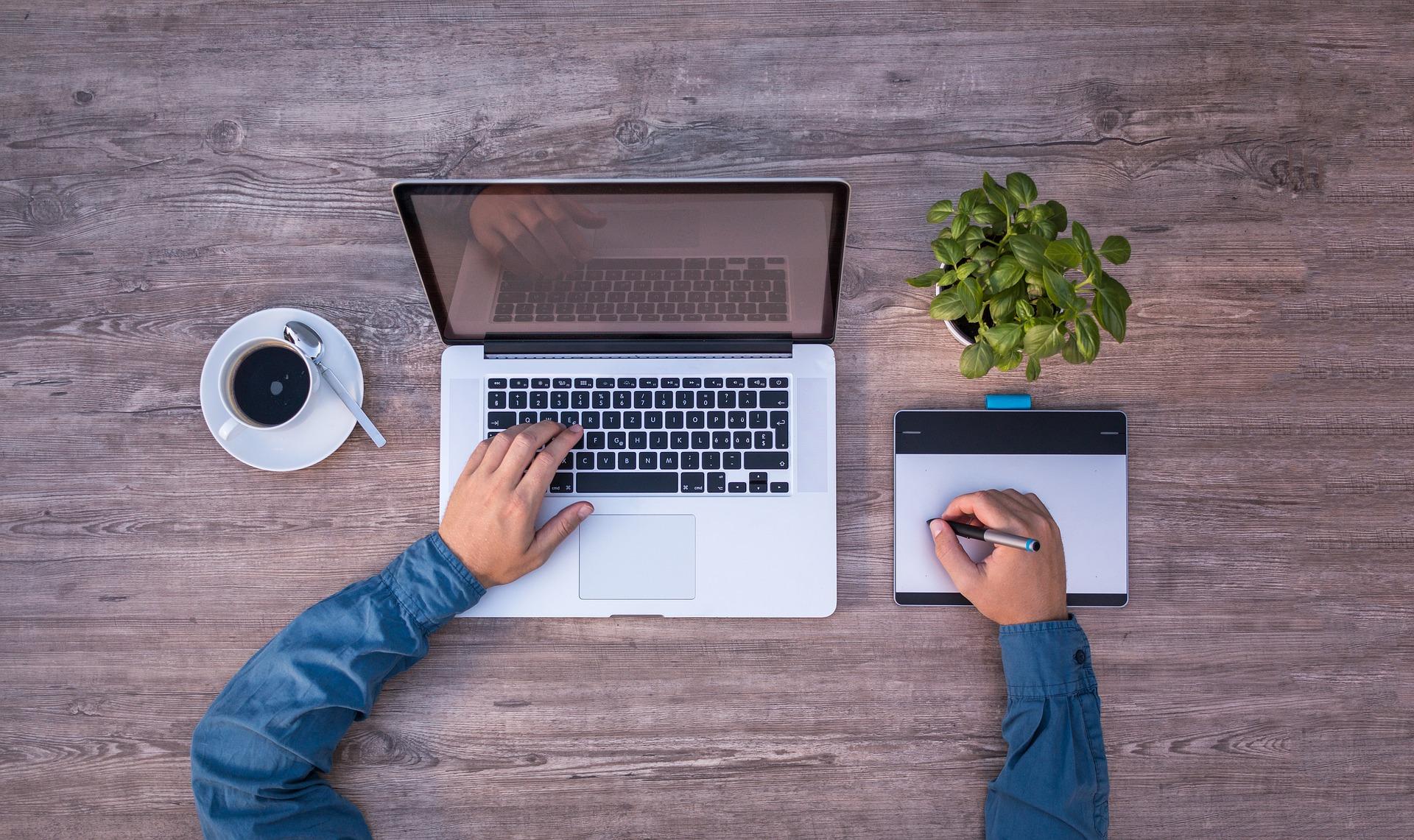 Imagem mostra uma pessoa usando uma mesa digitalizadora ao lado de um notebook.