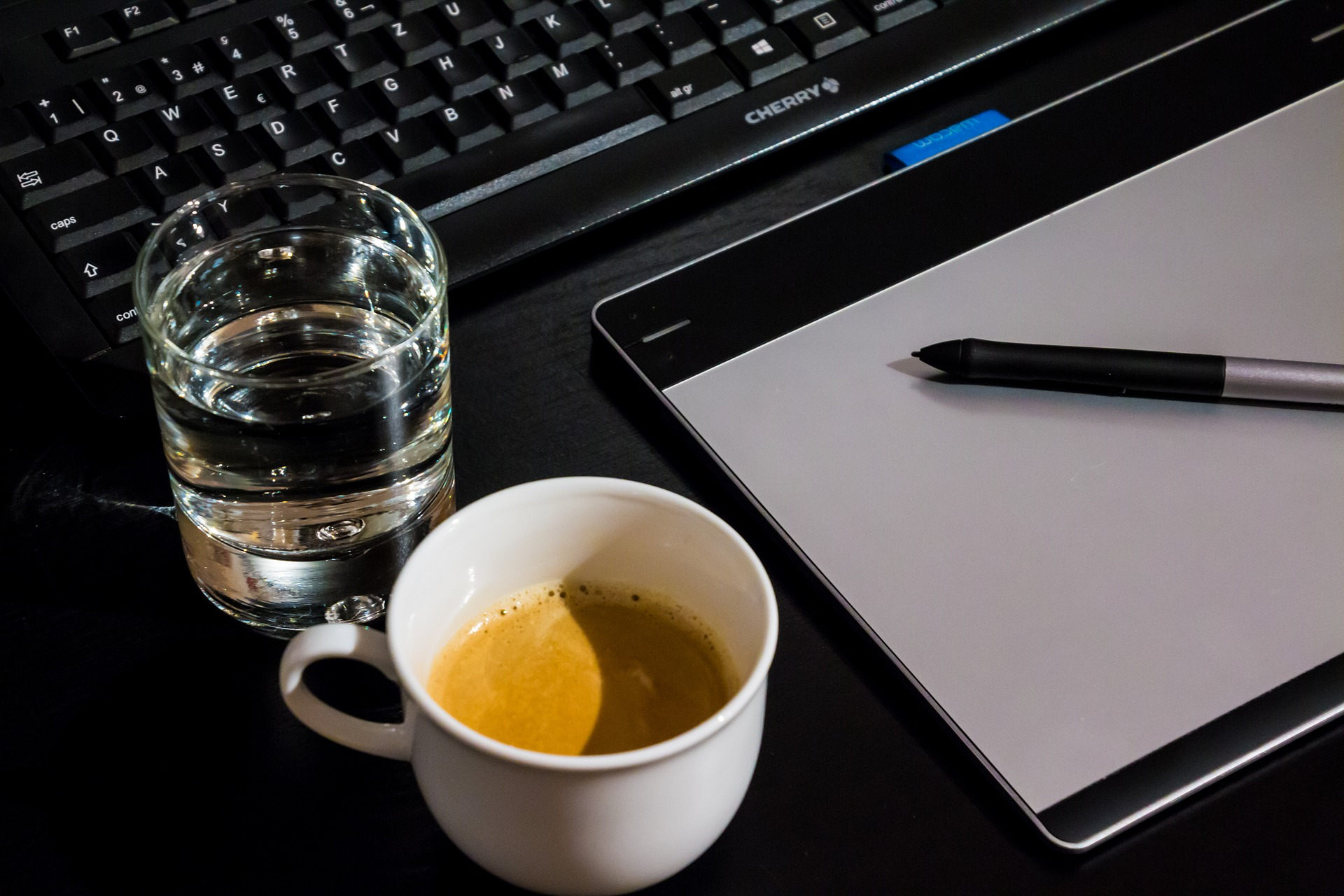 Imagem mostra uma mesa digitalizadora ao lado de uma xícara de café e de um copo d'água.