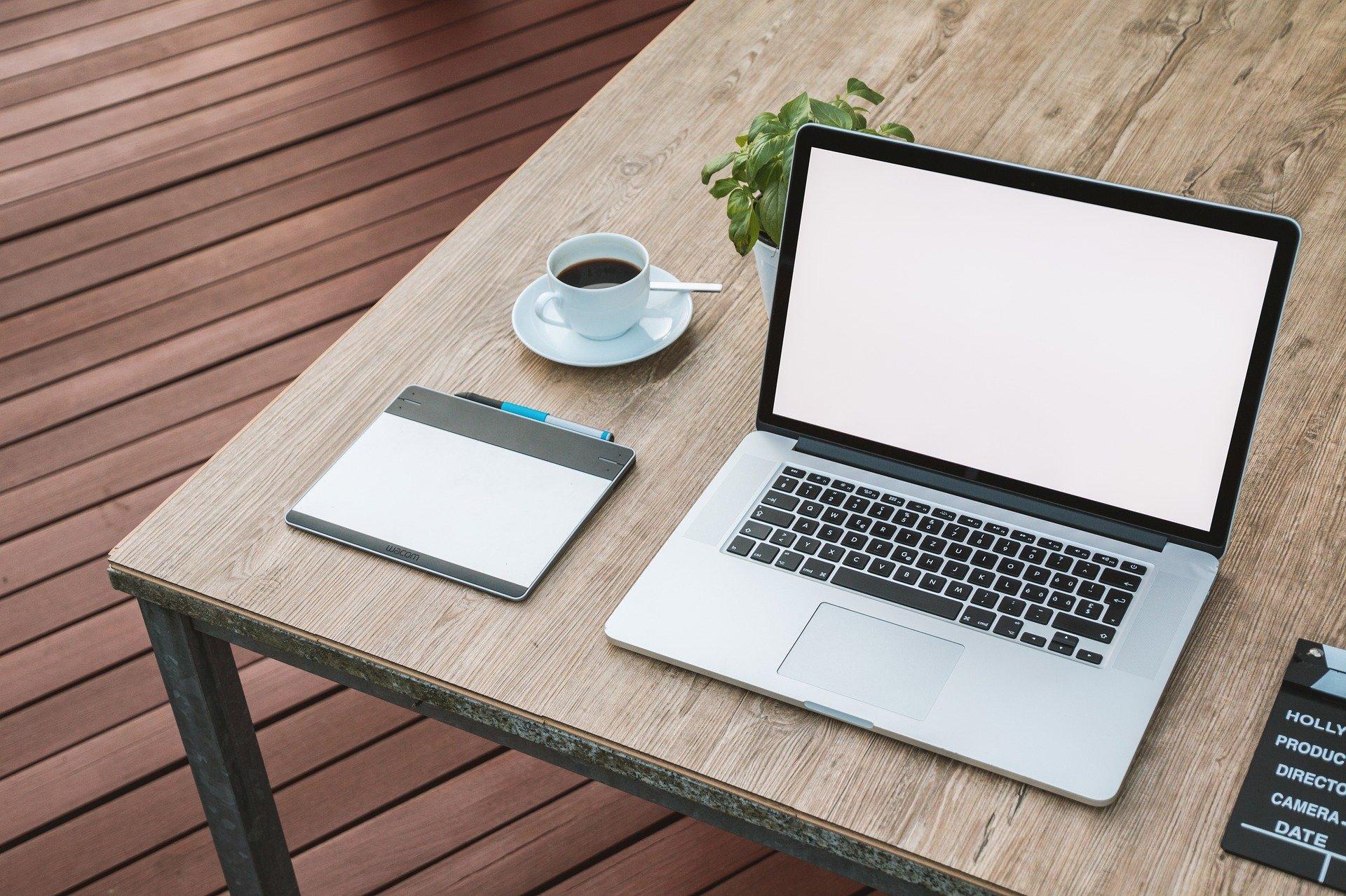 Imagem mostra uma mesa digitalizadora ao lado de um notebook e uma xícara de café.
