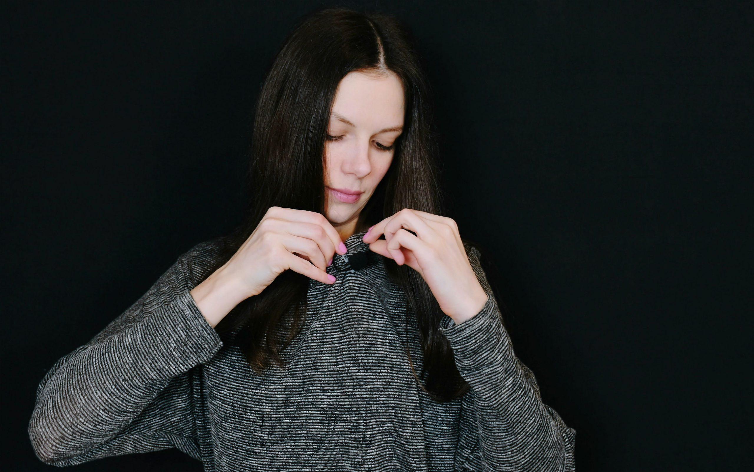 Imagem mostra uma mulher prendendo um lapela na roupa.