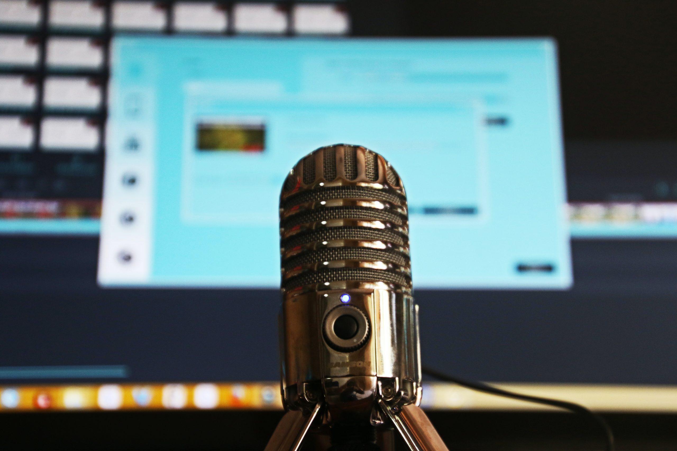 Imagem mostra um microfone em frente a um computador.