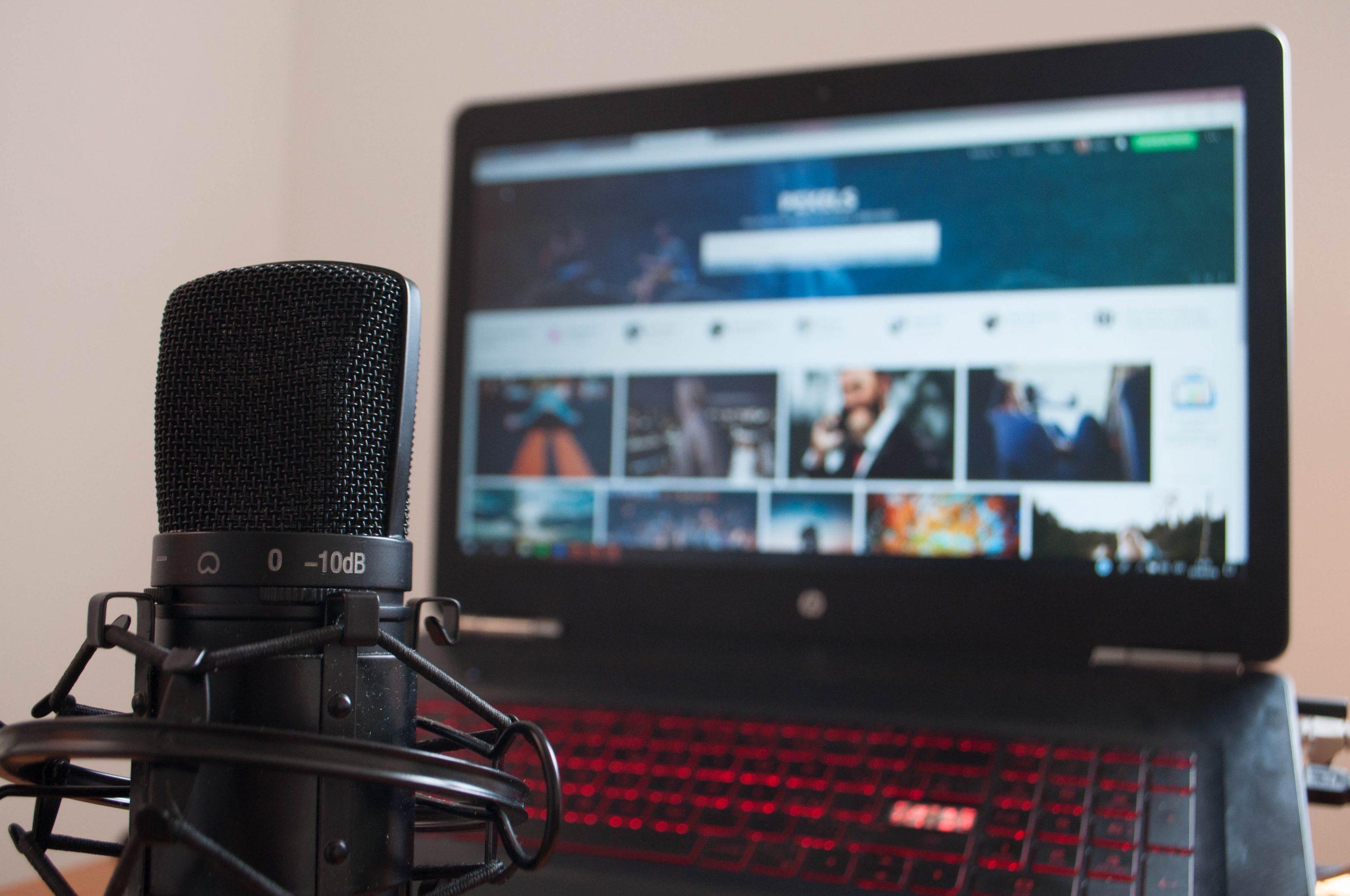 Imagem mostra um microfone em frente a uma tela de computador.