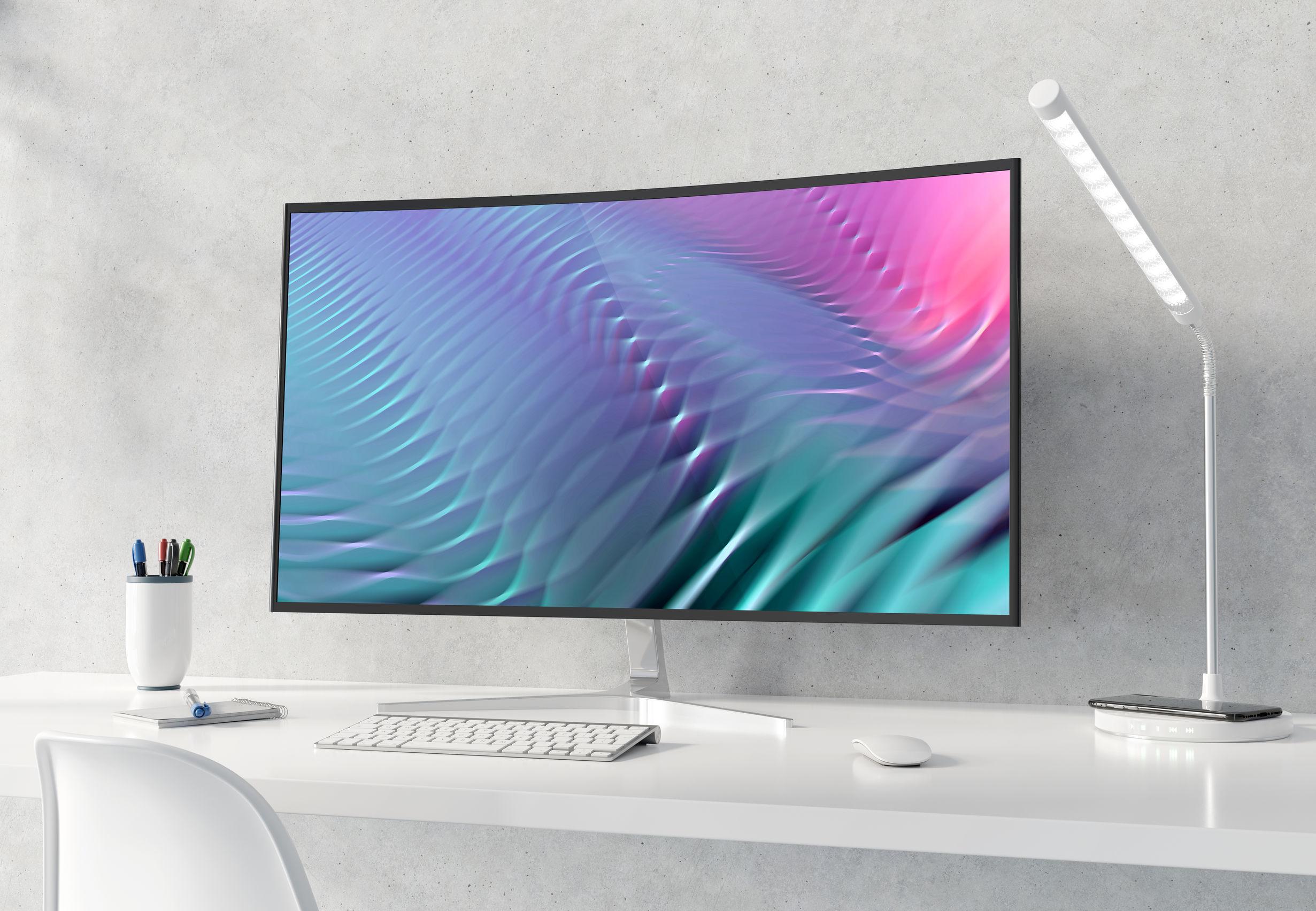 Imagem mostra um monitor curvo sobre uma mesa.
