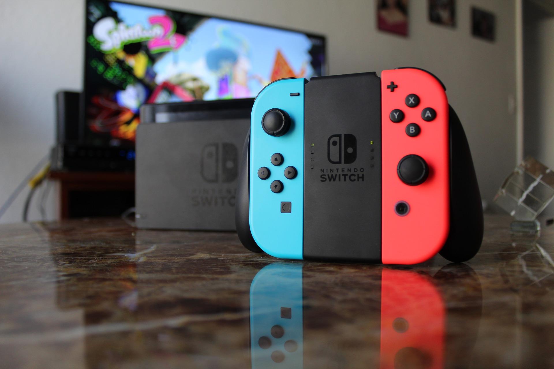 Imagem mostra um nintendo switch em primeiro plano com sua caixa e uma televisão ao fundo.