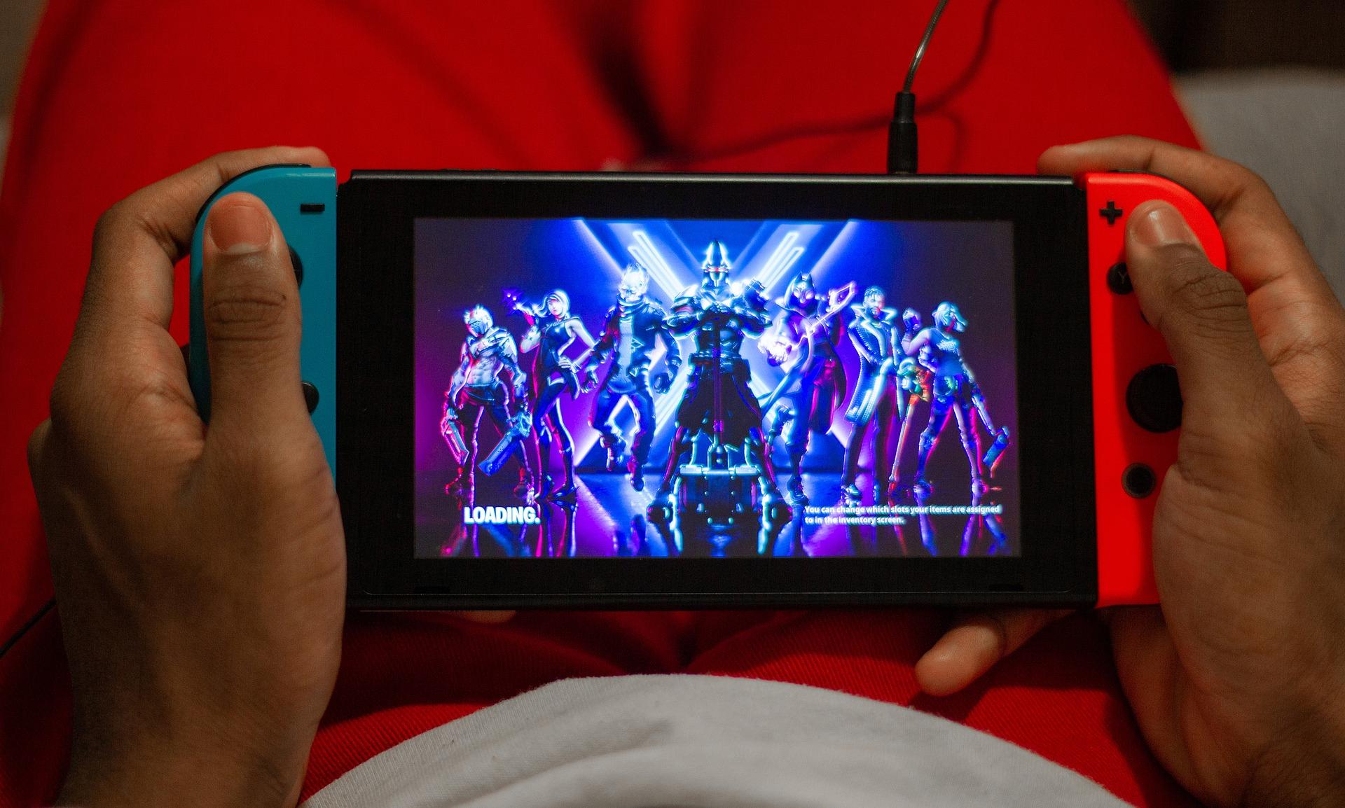 Imagem mostra as mãos de uma pessoa jogando Fortnite no Nintendo Switch.