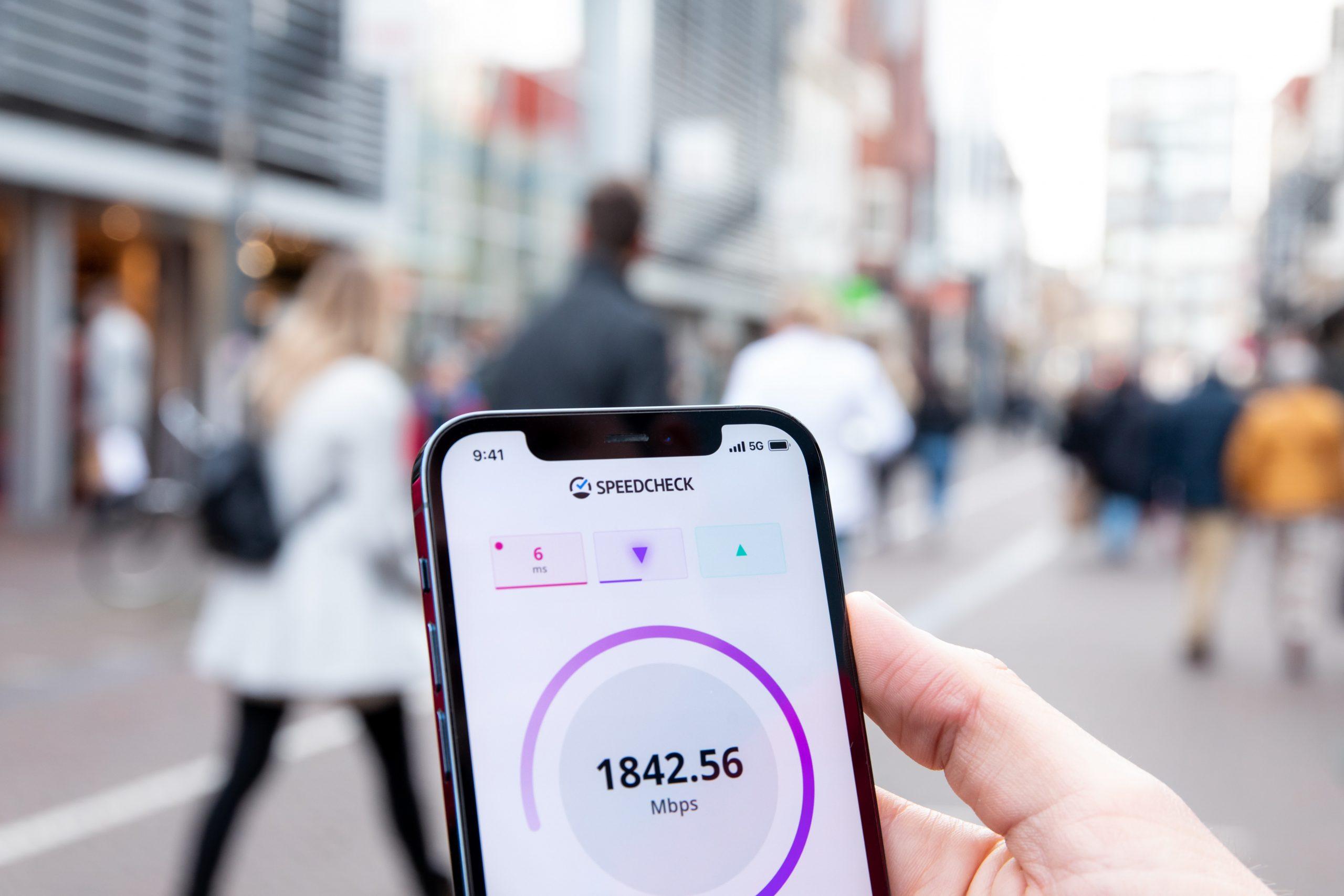 Imagem mostra uma pessoa segurando um celular que mostra o resultado de um teste de velocidade de conexão.