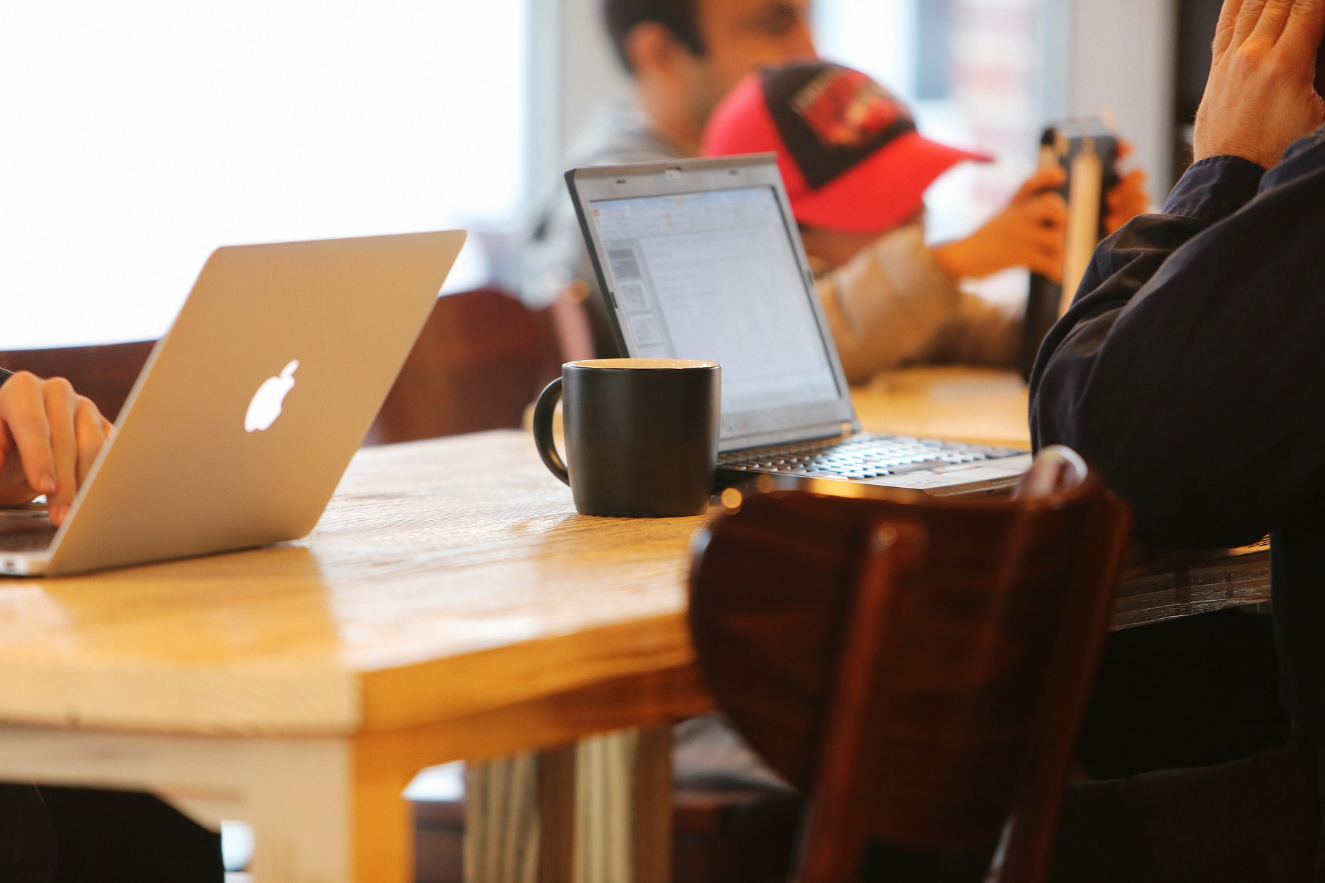 Imagem mostra uma sala com várias pessoas usando notebooks.