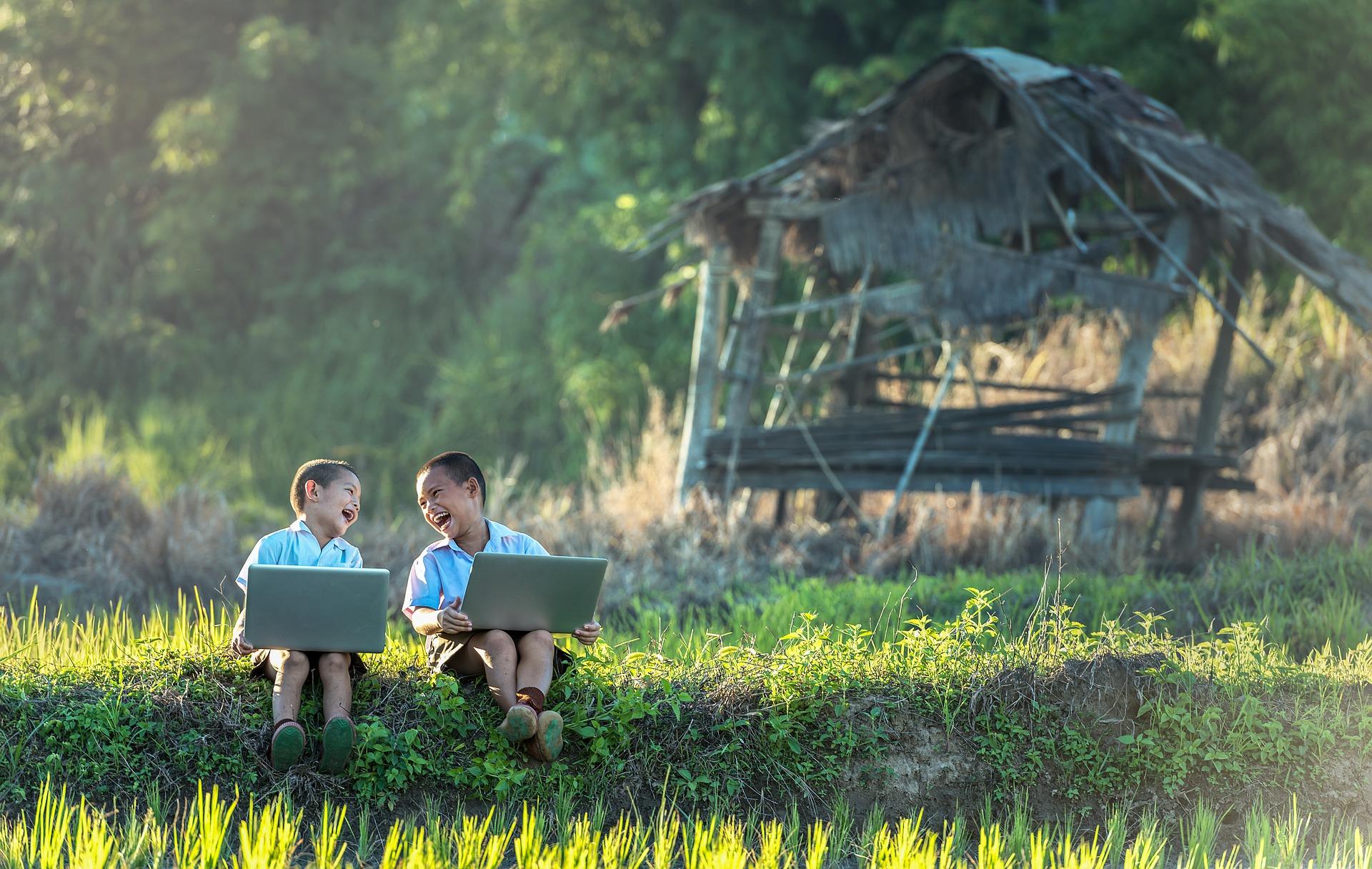 Imagem mostra duas crianças usando notebooks em uma área externa.