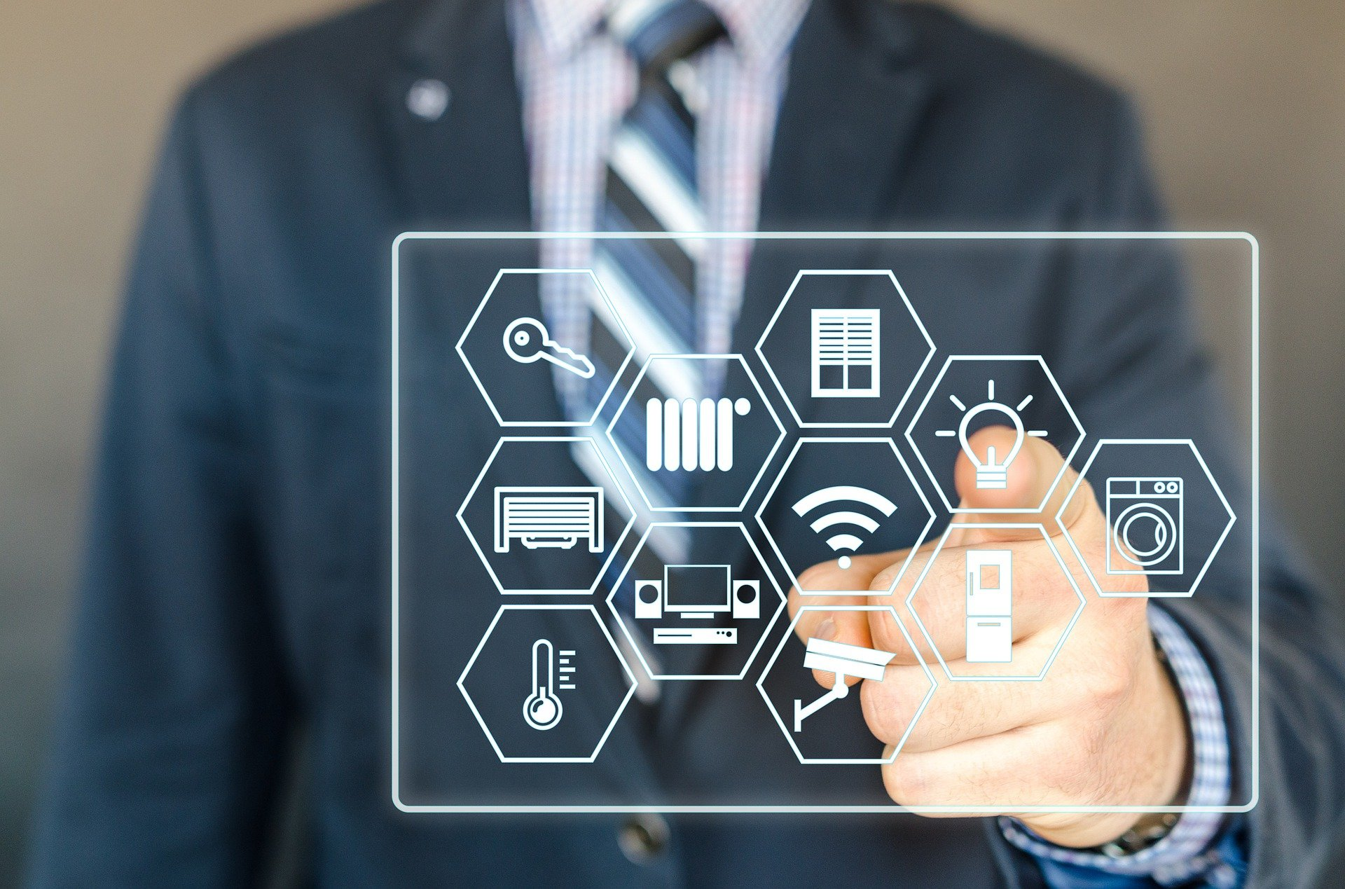 Imagem mostra uma pessoa controlando um painel digital com ícones de objetos domésticos.