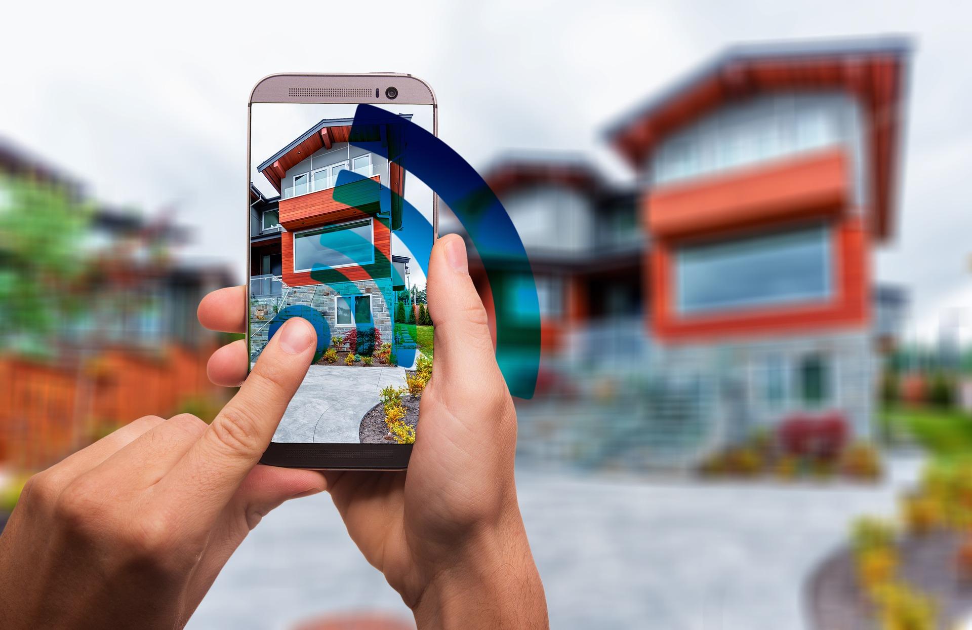 Imagem mostra uma pessoa usando um celular em frente a uma casa.
