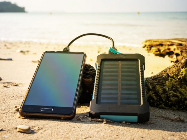 Battery solar energy device on a background of the sandy beach of an uninhabited island. Charge smart phone from the solar battery. the solar battery lies on a wooden log. Modern frameless smartphone