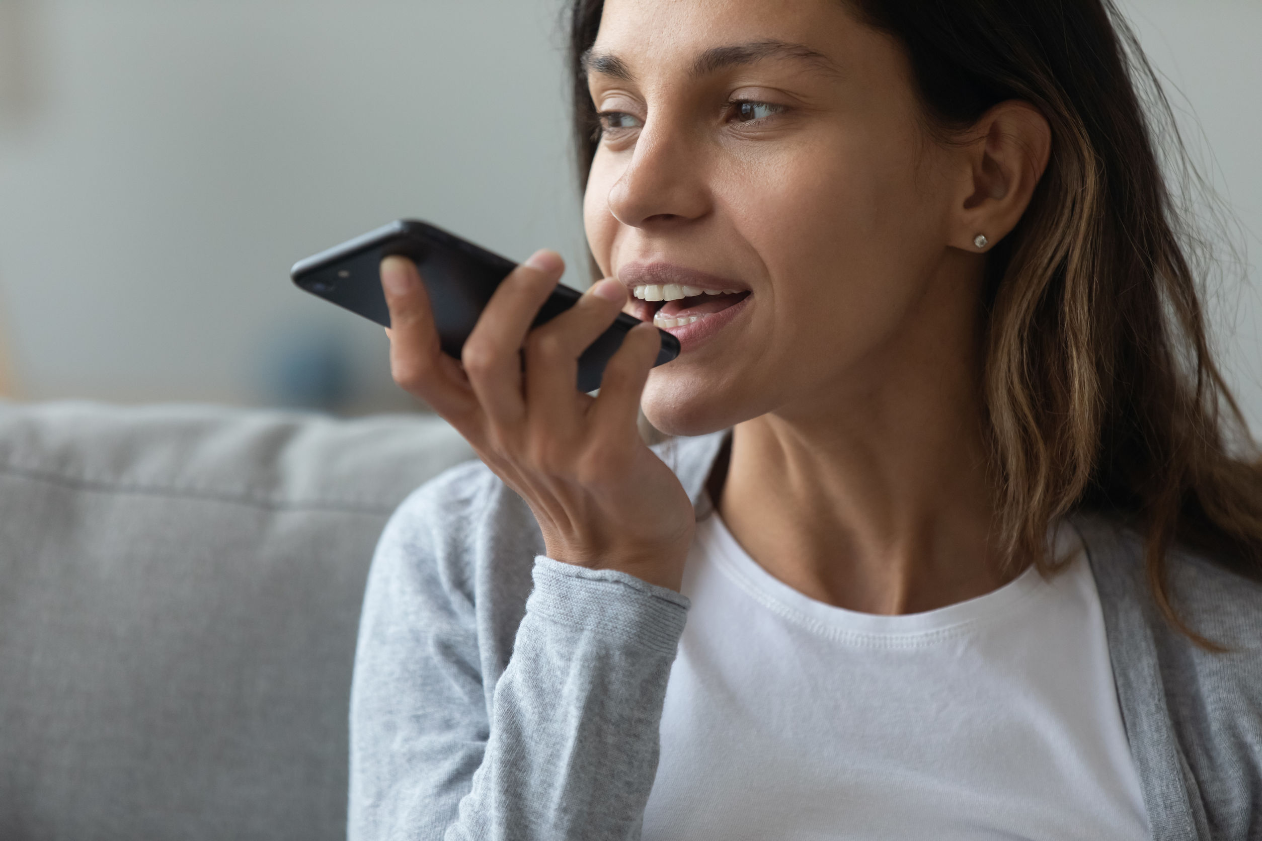 Imagem mostra uma mulher falando junto a um pequeno dispositivo.