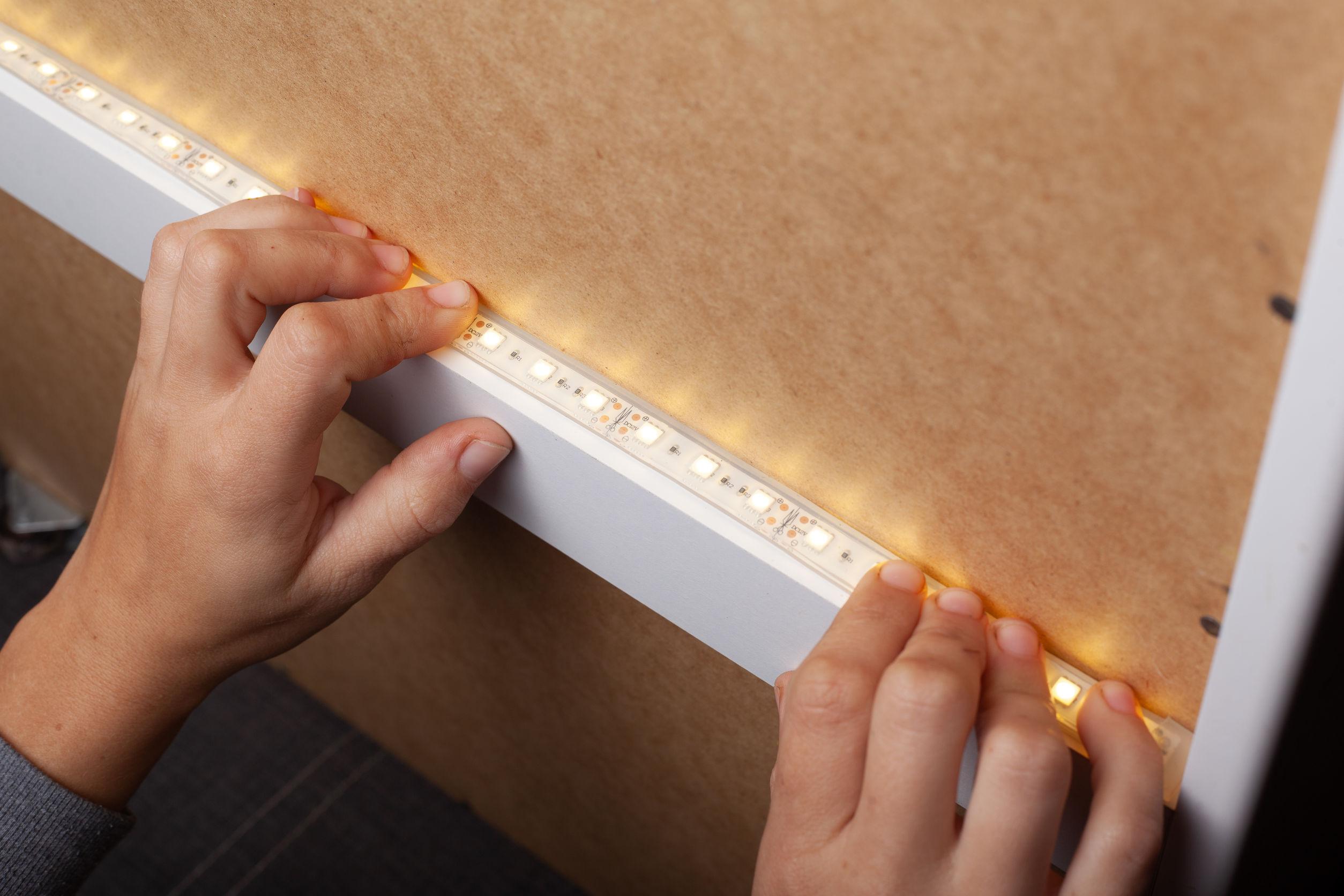 Imagem mostra uma pessoa instalando uma fita de LED.