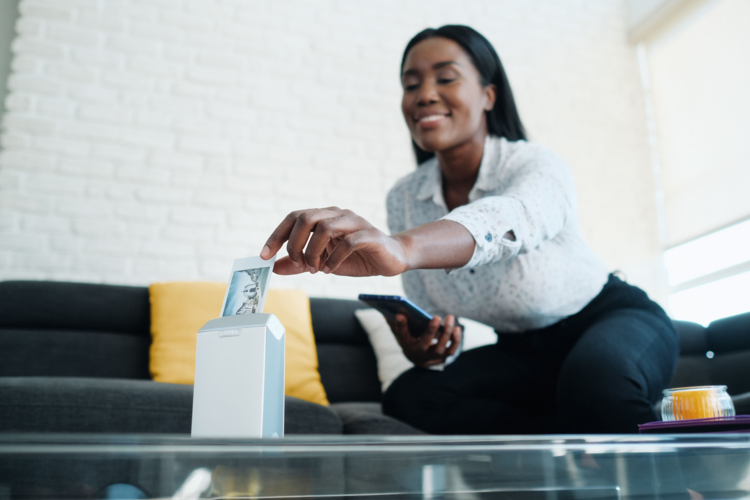 Imagem mostra uma mulher imprimindo uma foto com uma impressora portátil.