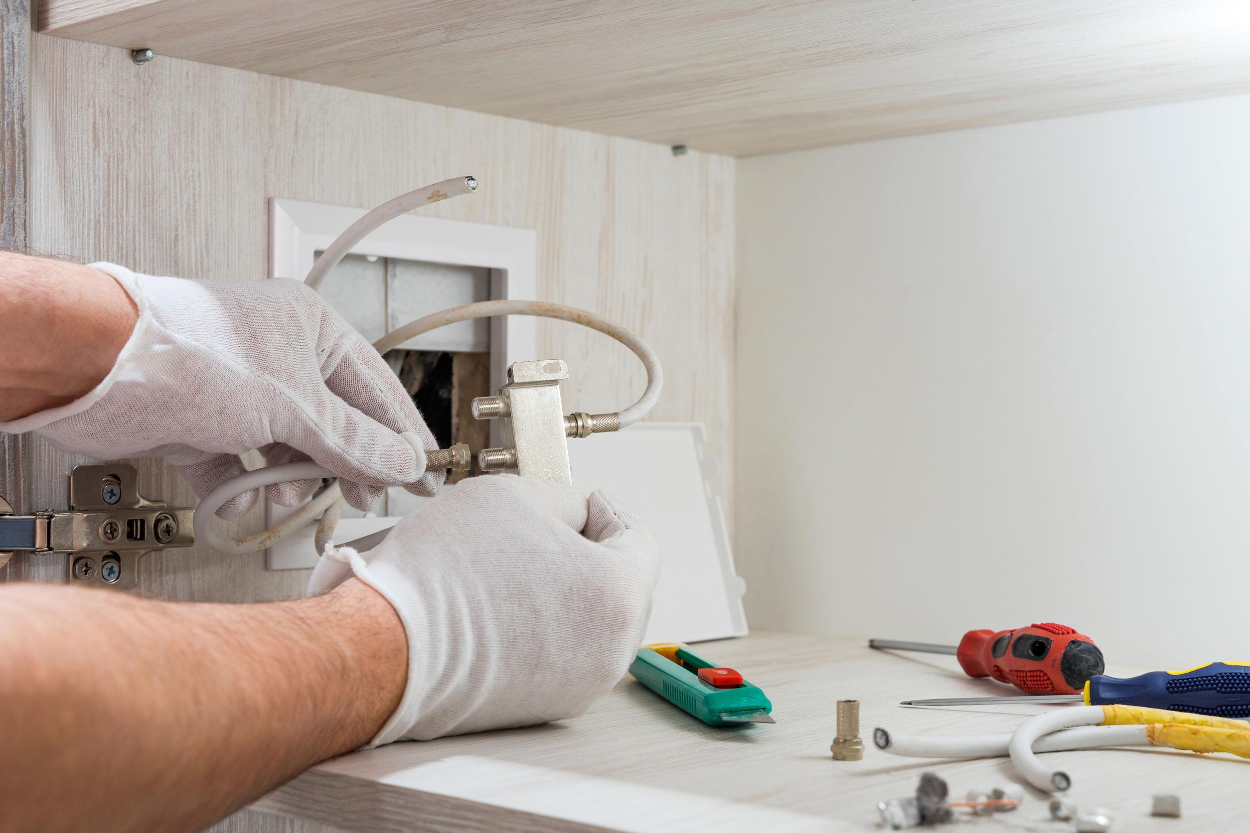 Imagem mostra uma pessoa instalando um splitter.